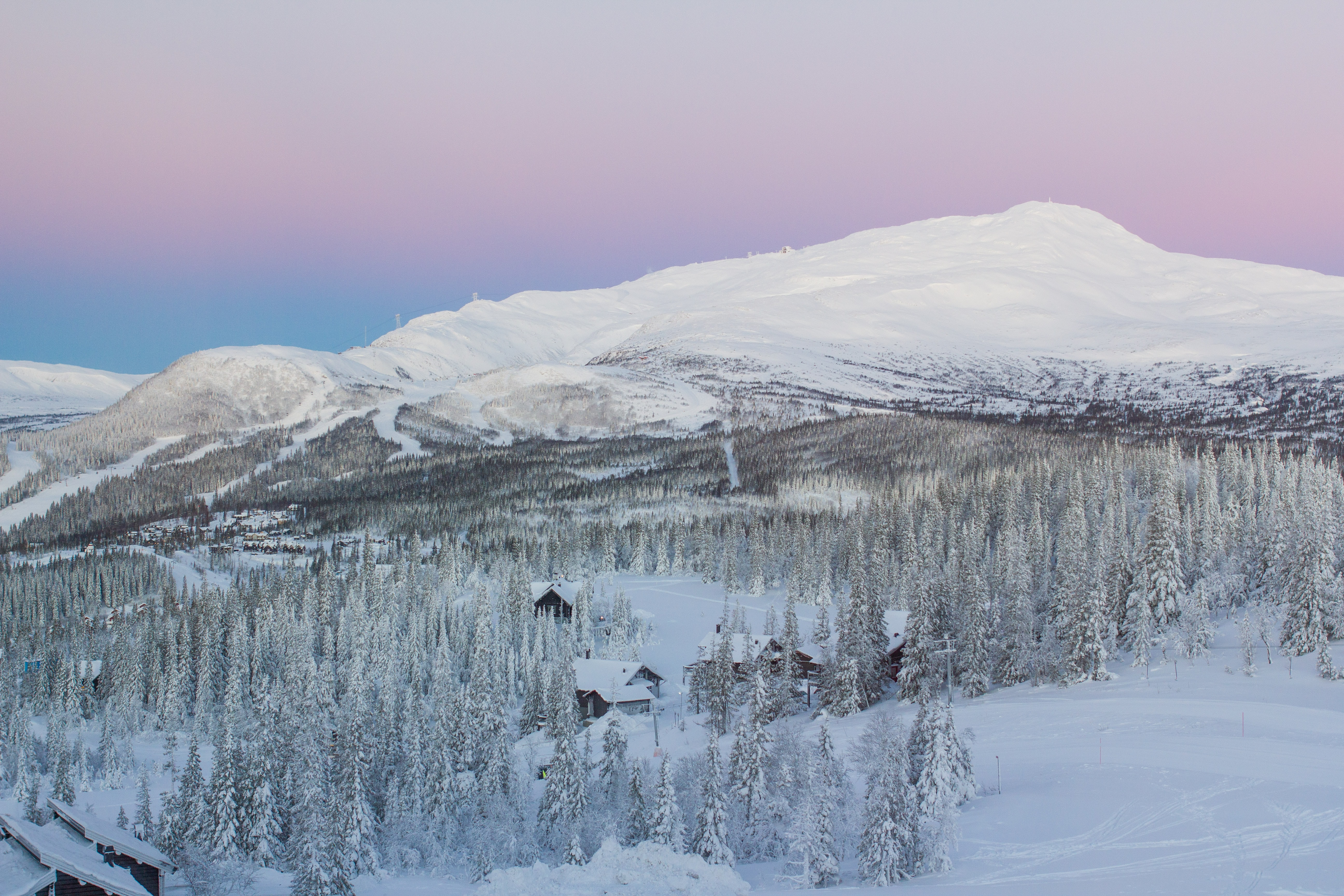 A pink and purple sunrise behind a snow laden mountain and trees near a homestead