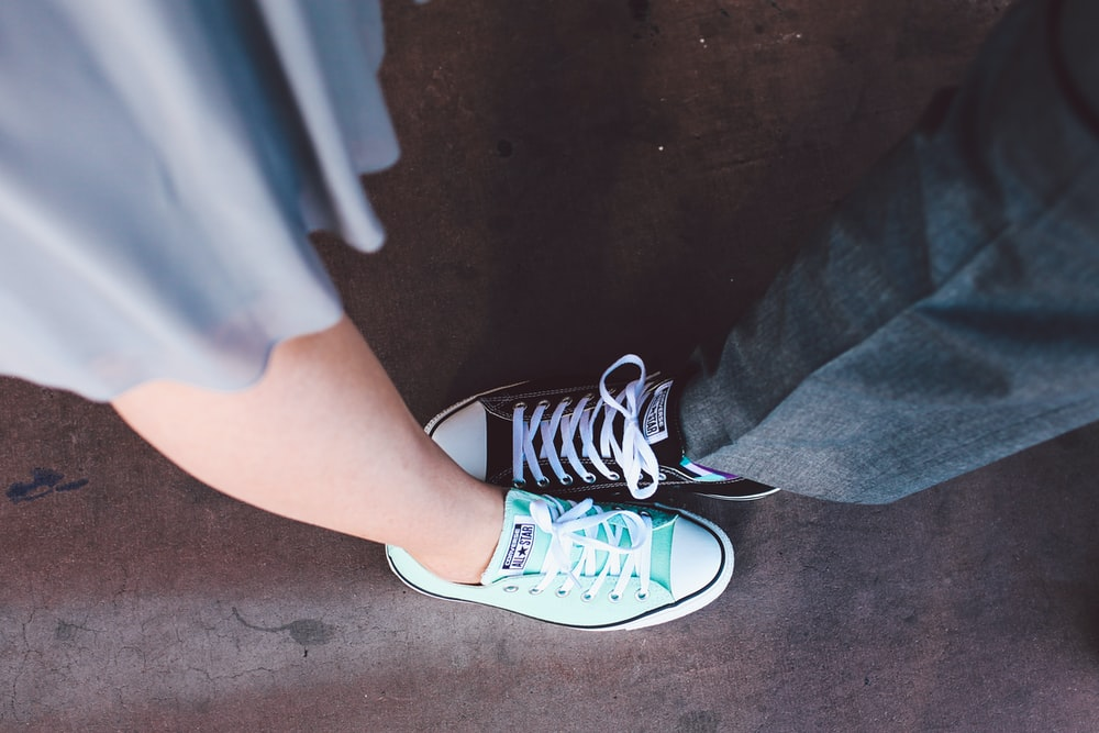 person wearing teal and white Converse All-Star low-top