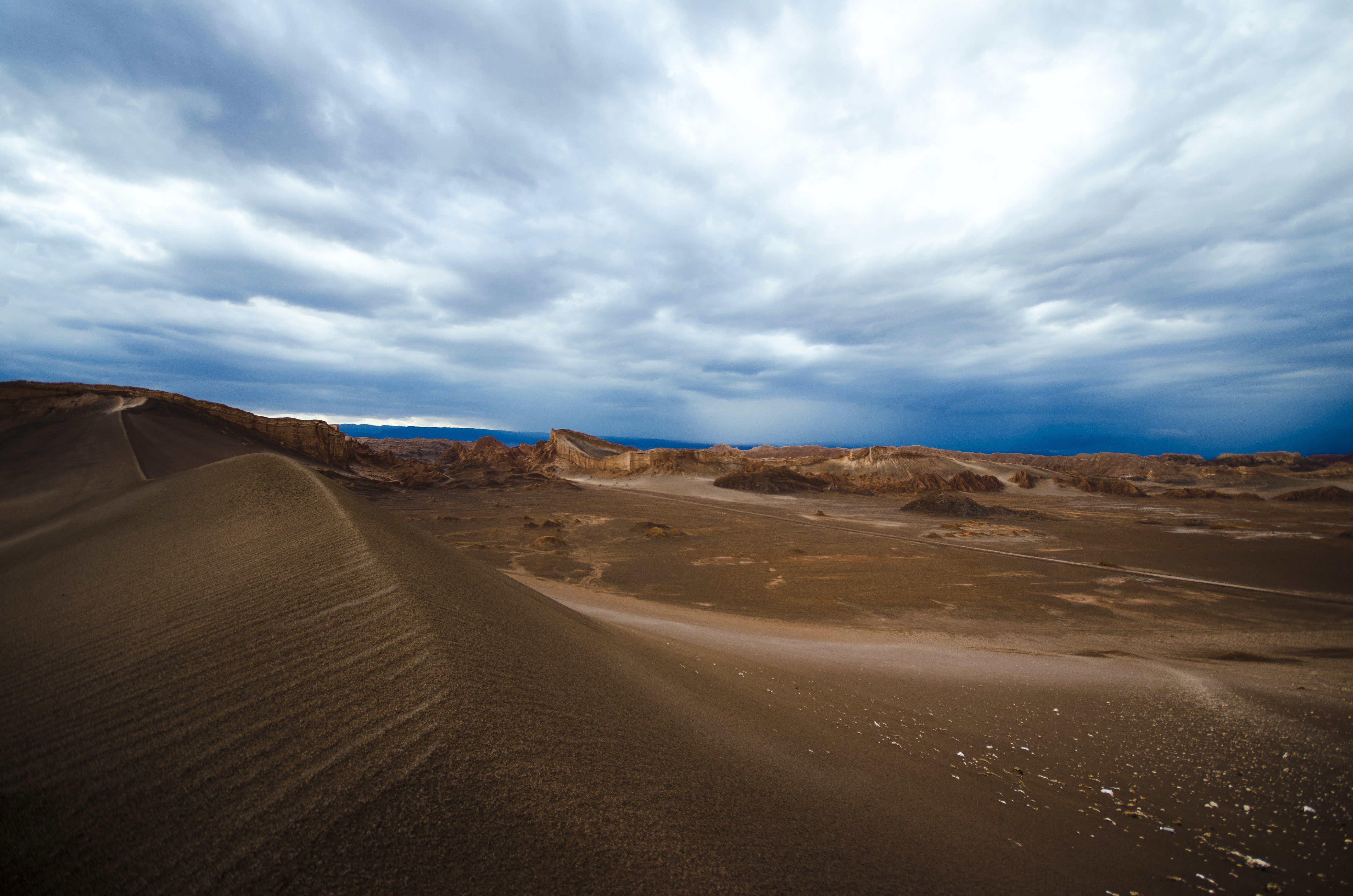Clouds on a bright day over the sand dunes in Atacama Desert