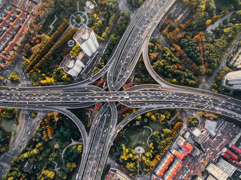Drone view of busy highway interchange surrounded by buildings and trees in Shanghai, China