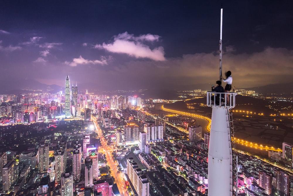 two person on white meta tower at nighttine