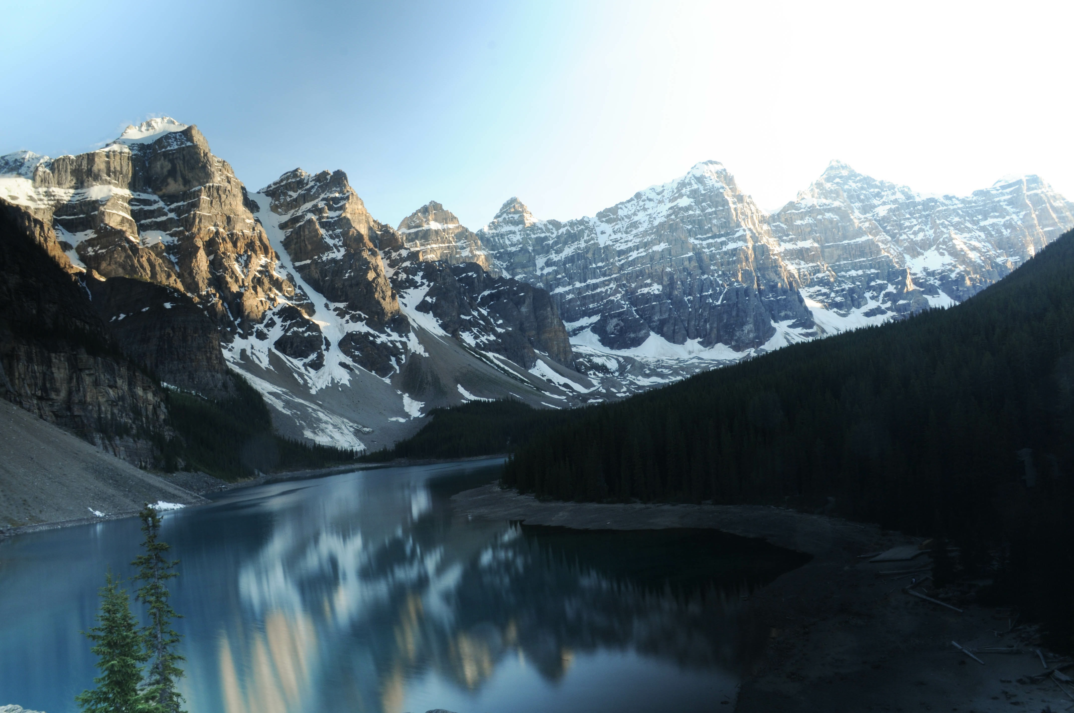 The Moraine Lake is showing a reflection of the snowcapped mountains surrounding it