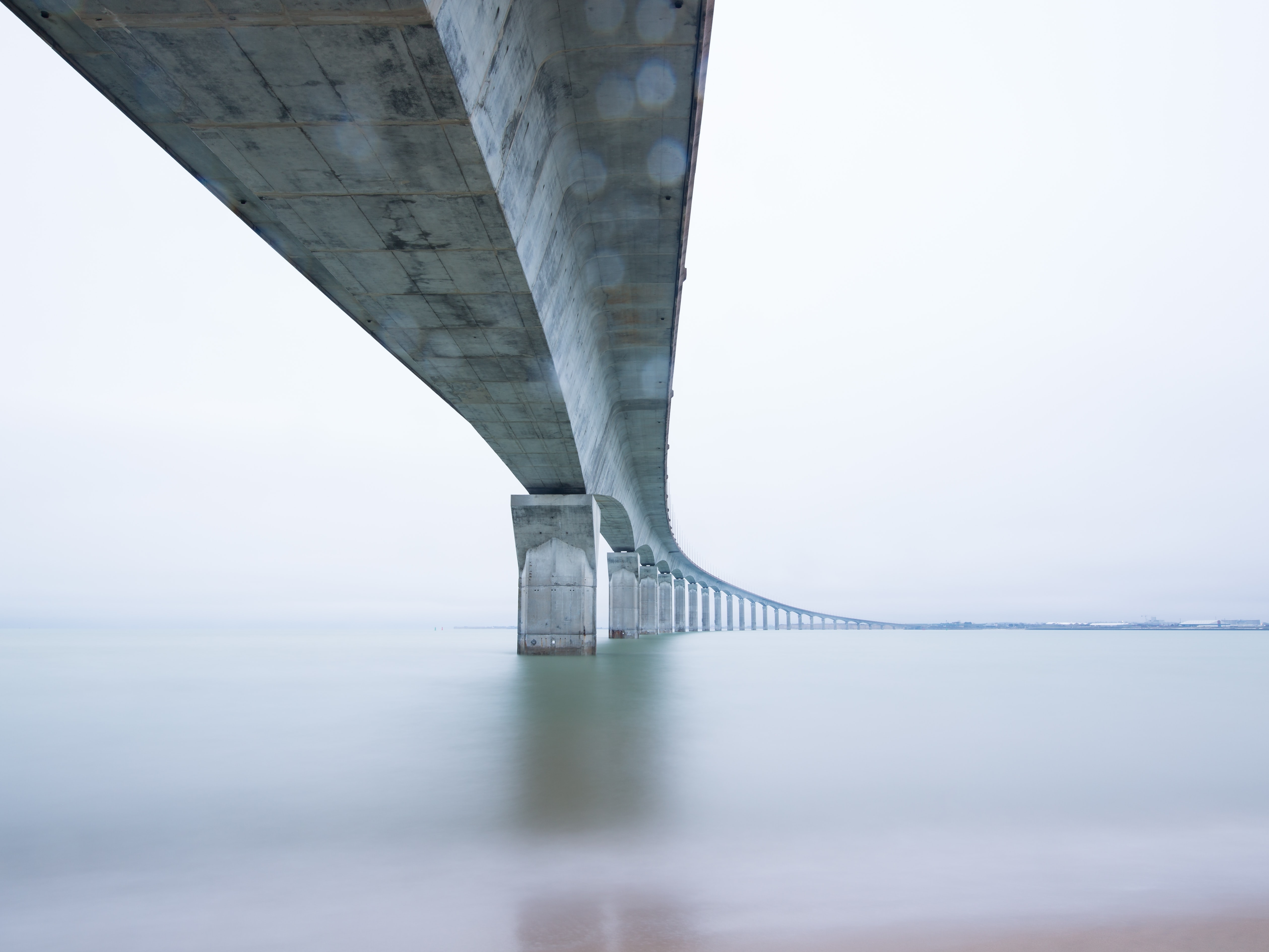 A long curved concrete bridge on a cloudy day