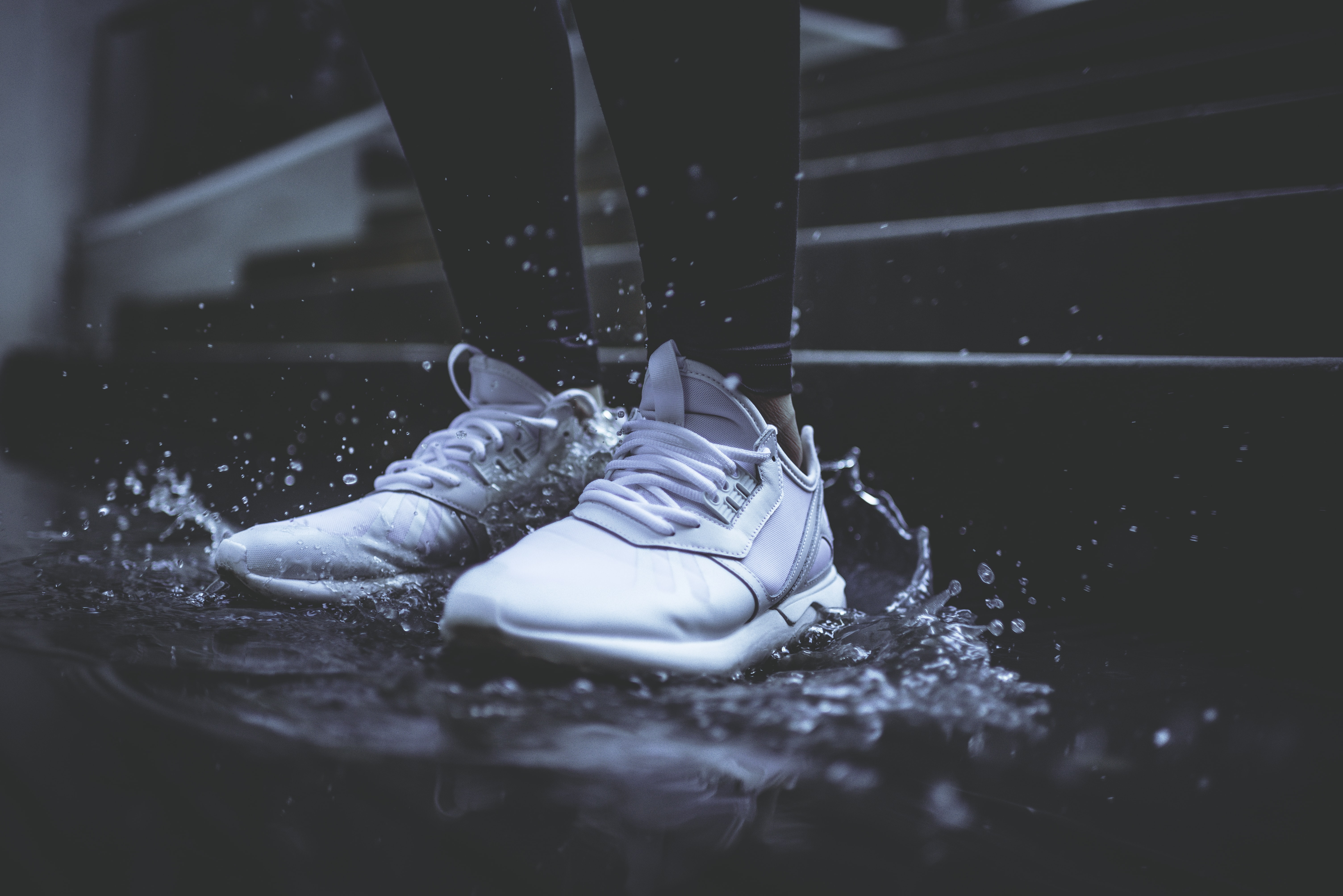 A pair of white shoes splashing into a puddle on a London street