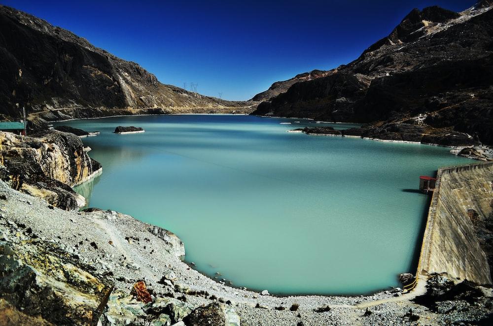 dam within mountain range during daytime