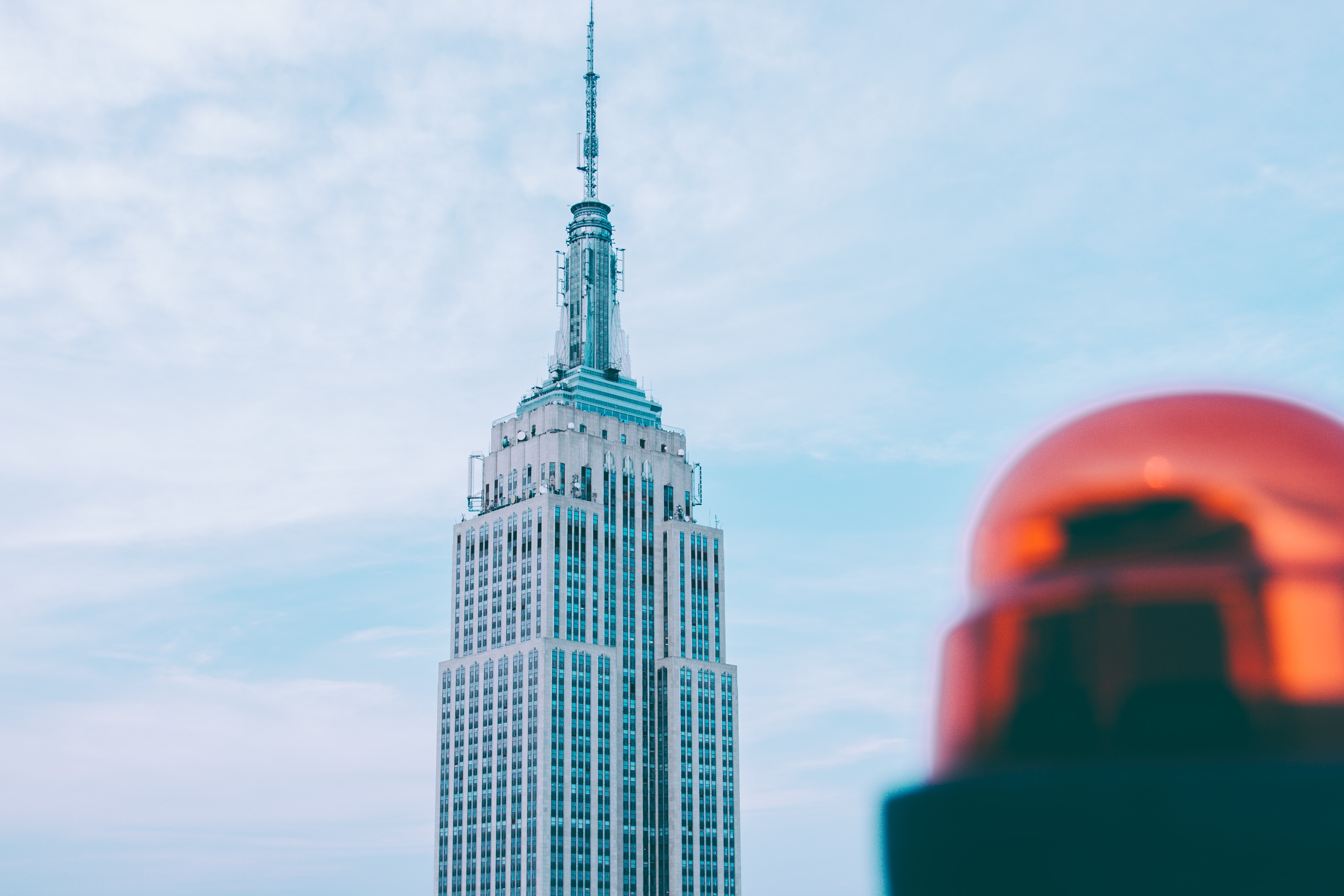 View of the top of the Empire State Building with blue sky behind it