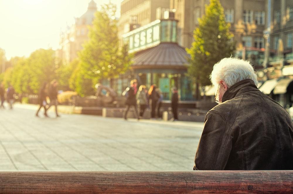man sitting on brown wooden bench