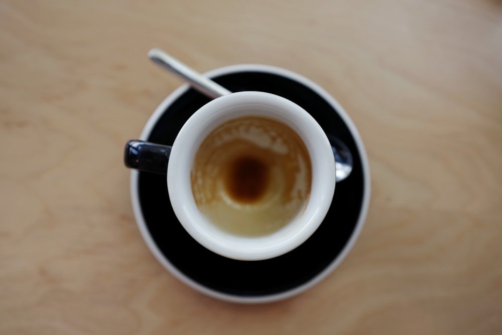 coffee in mug on saucer beside spoon