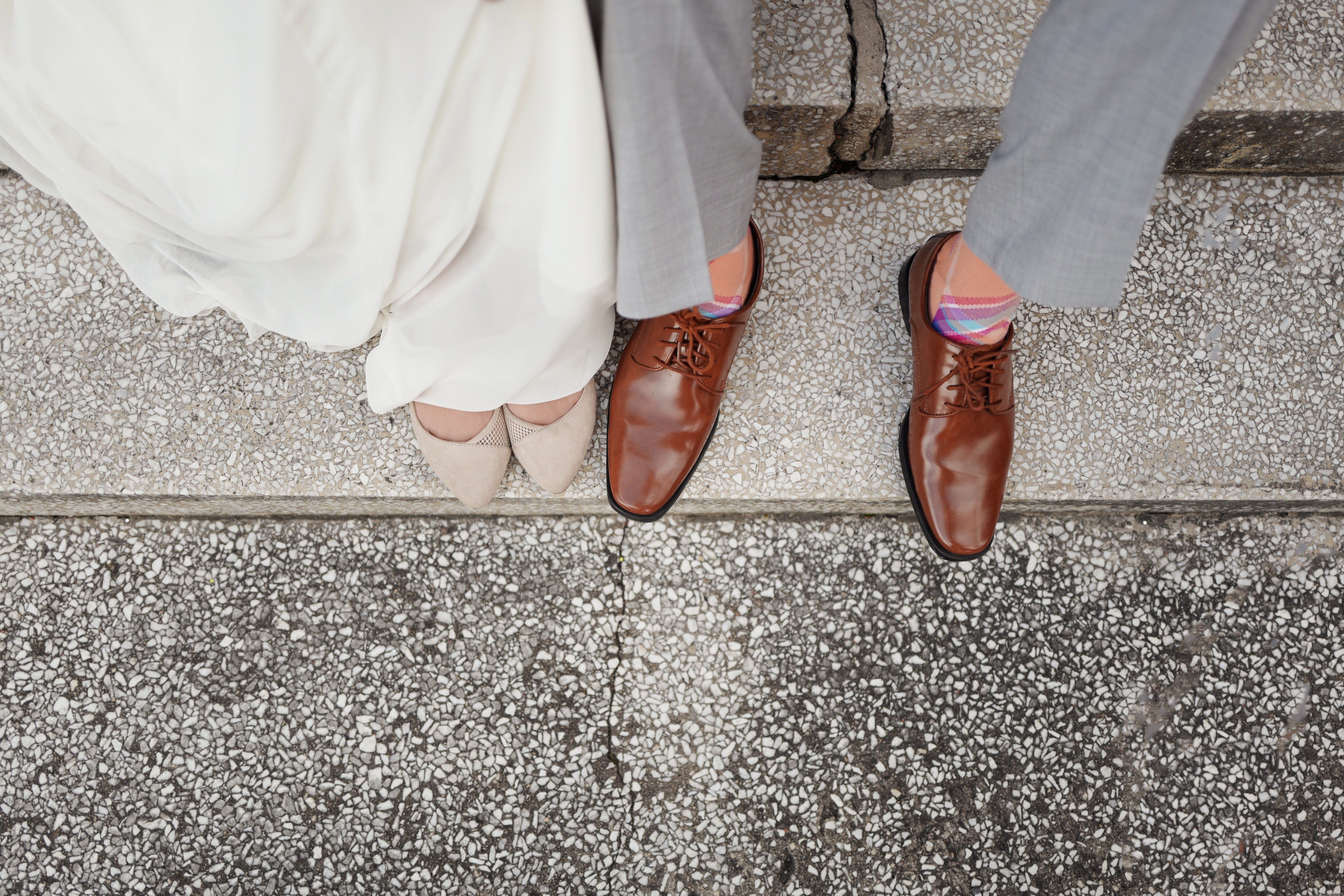 A couple's feet on their wedding day, showing off their dress shoes. He wears colorful socks.