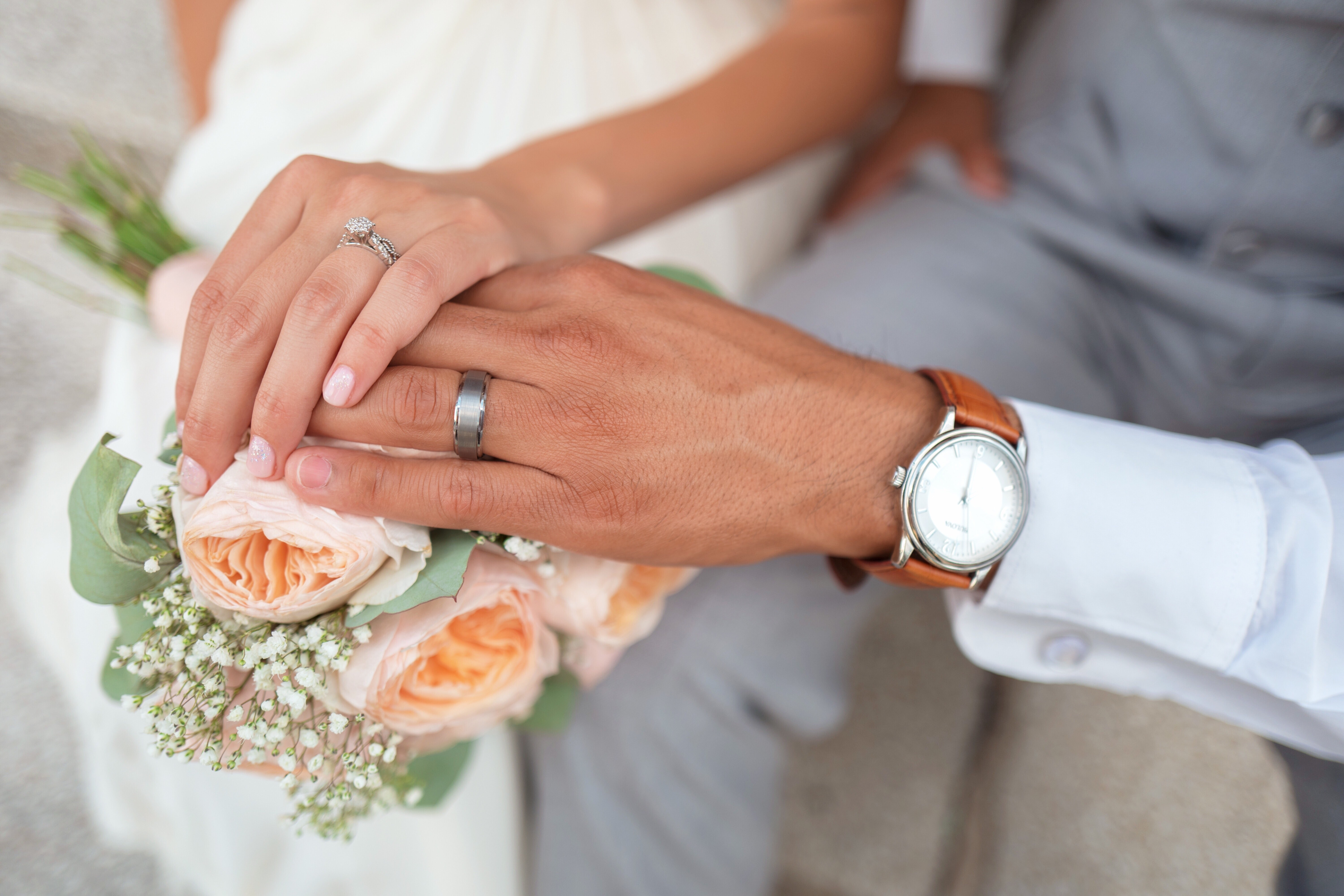 Bride and groom's hands touching over wedding bouquet