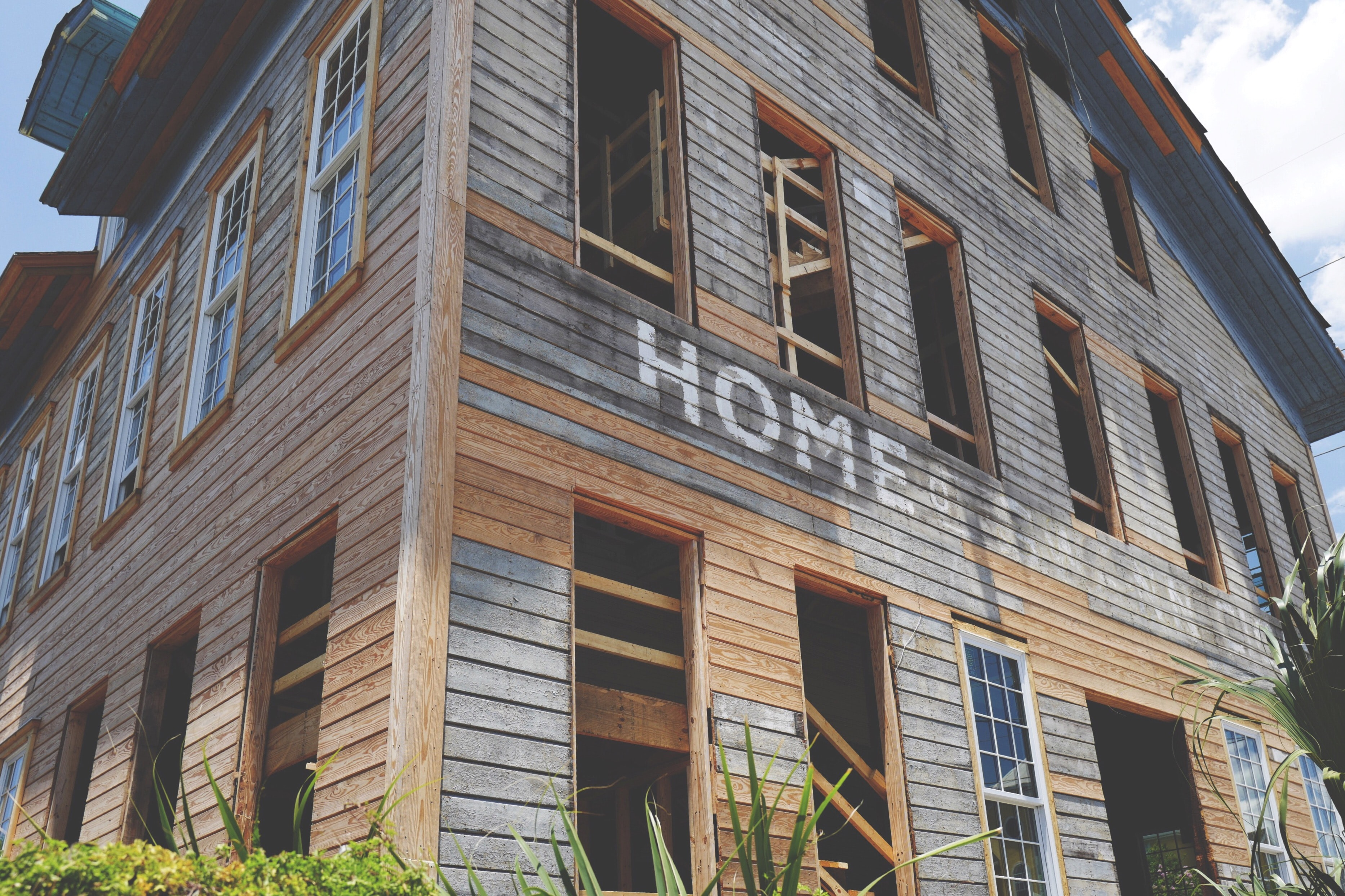An old wooden building with a fading painted sign on it is being restored