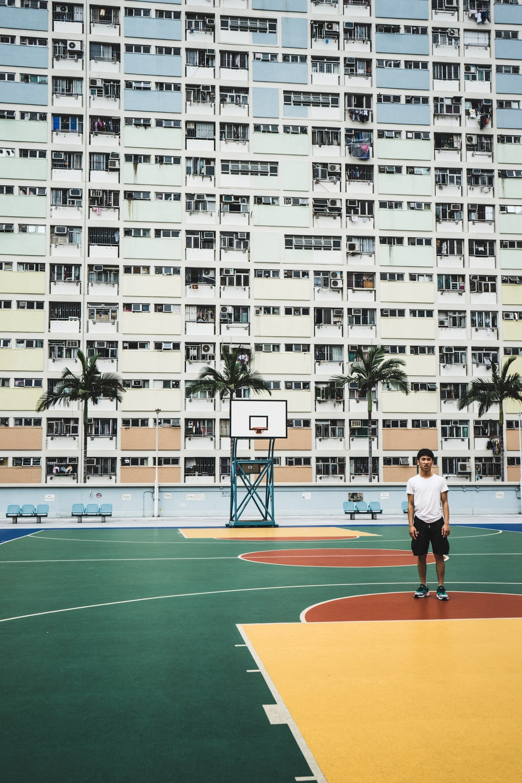 man standing on basketball court near building
