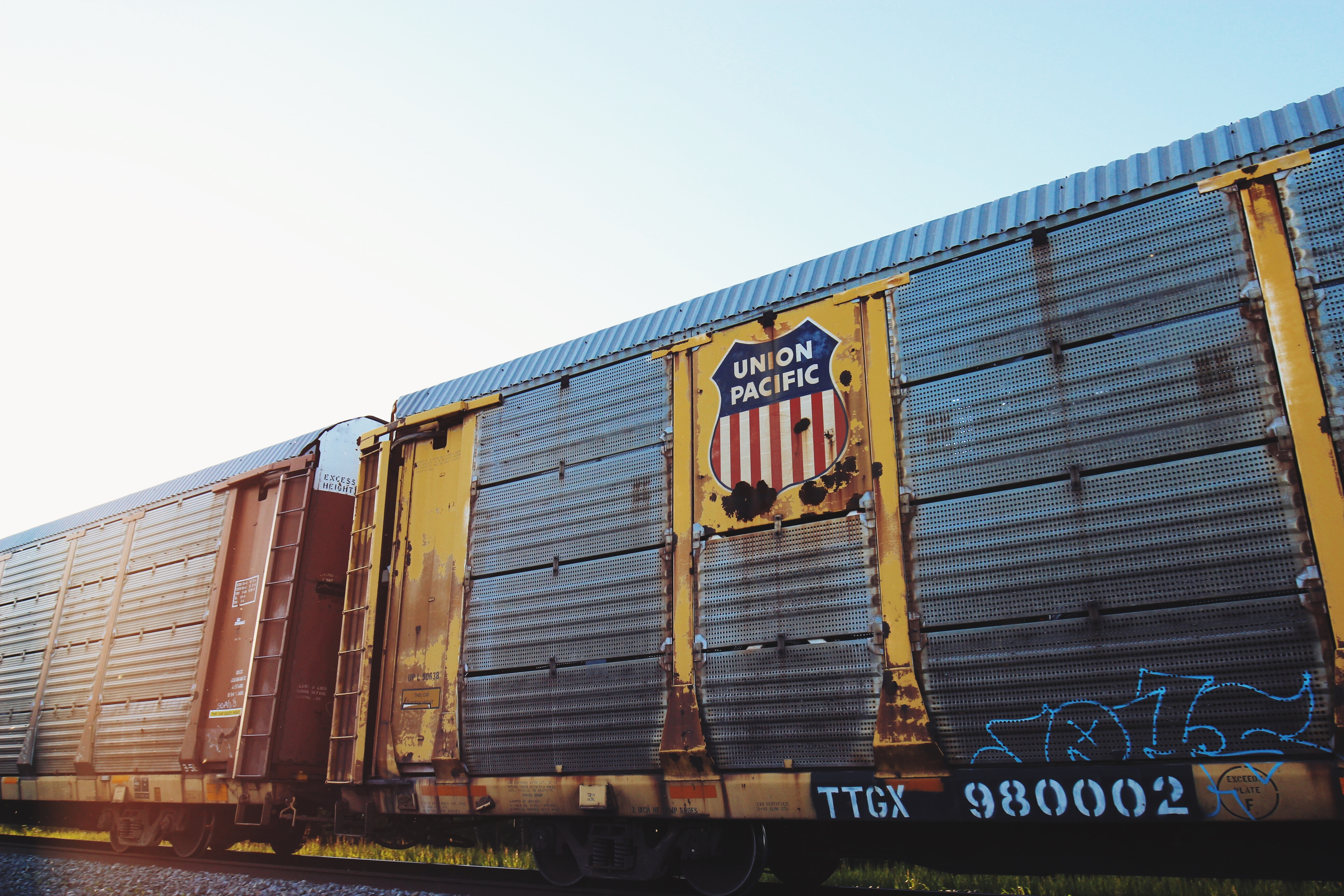 An old rusting Union Pacific railcar with blue graffiti on it passing a grassy area under a clear sky