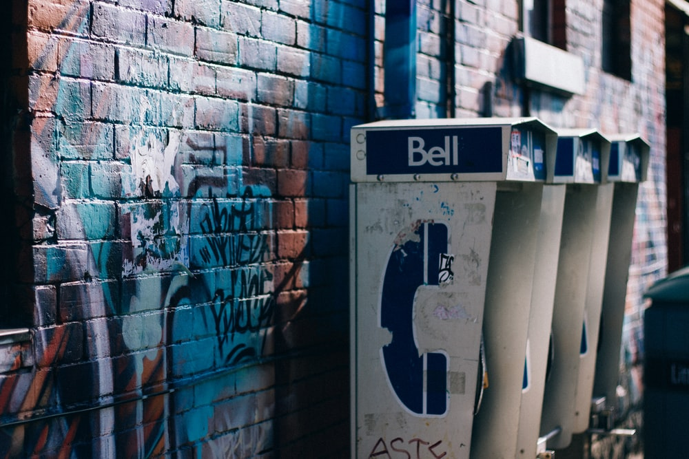 white and black Bell phone booth beisde concrete bricked wall with graffiti