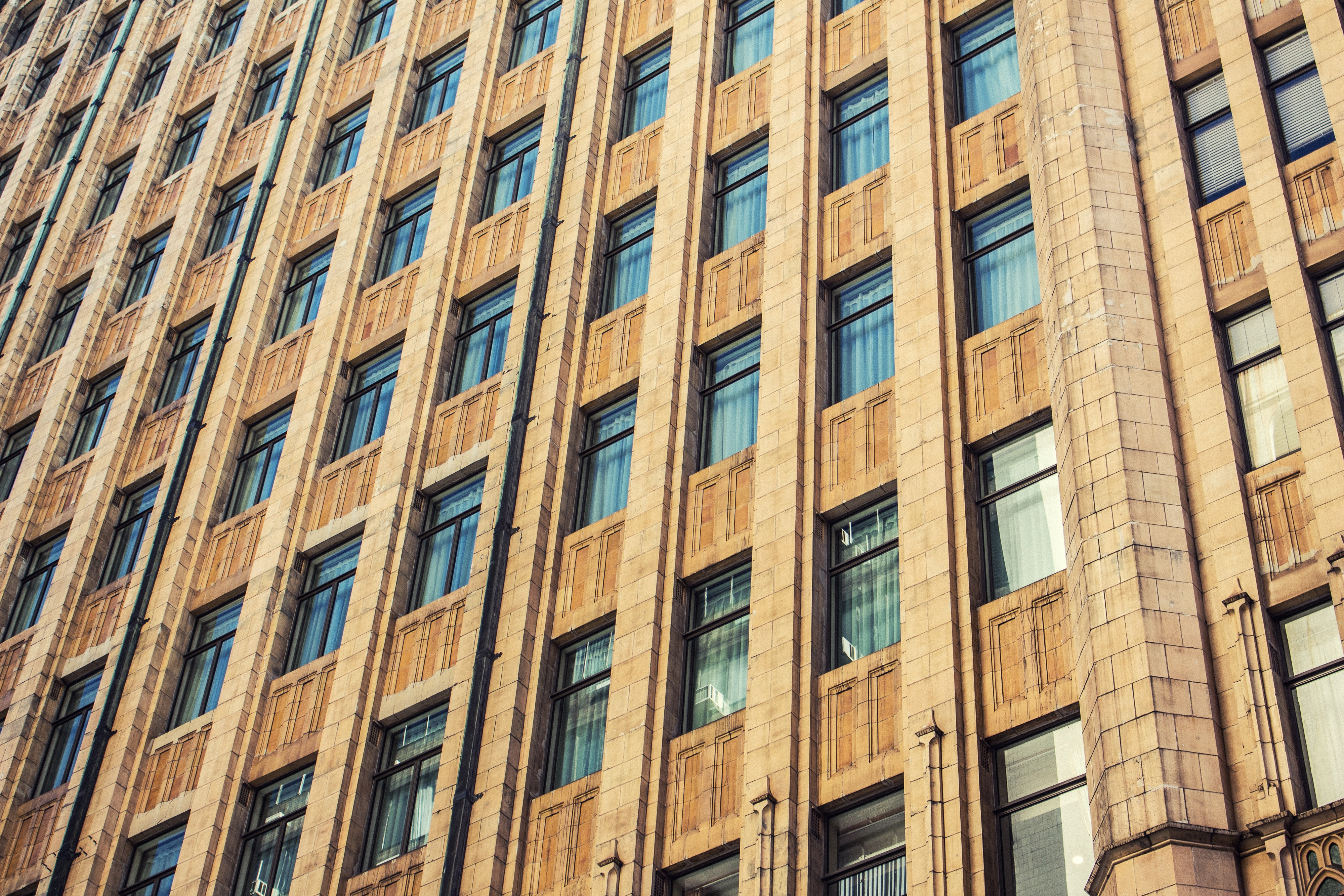 Facade of apartment building in the city with brown exterior and reflective windows in a pattern