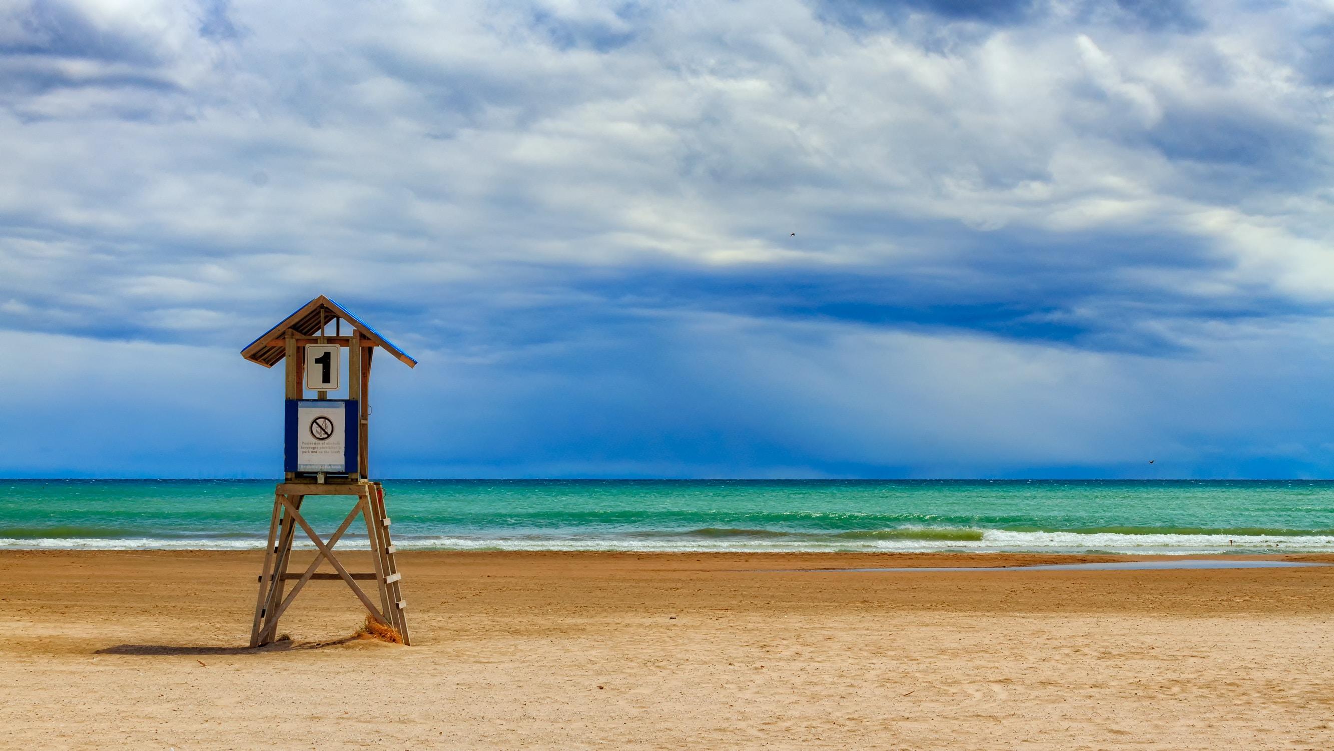 A lifeguard stand on a deserted beach along a green ocean under a blue sky