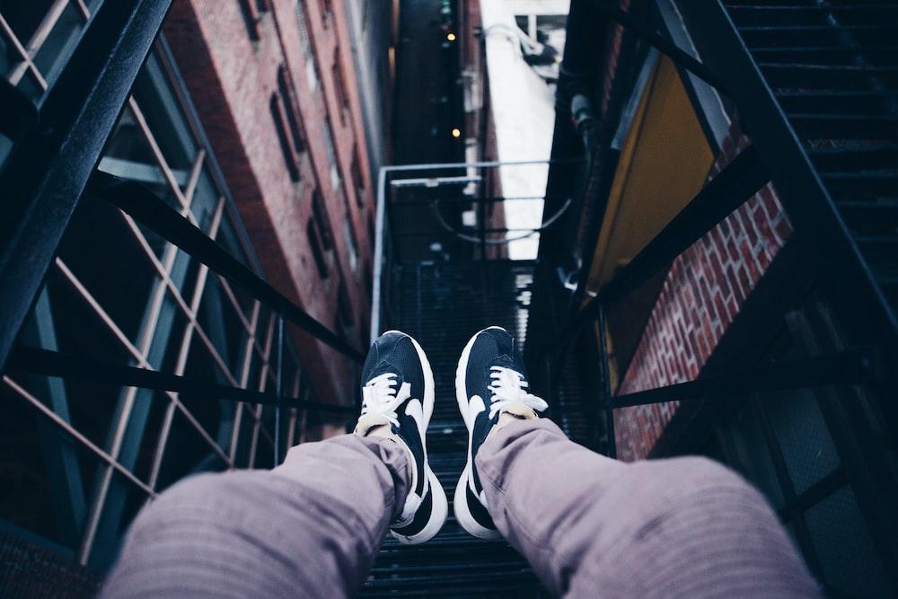 person wearing pair of black Nike shoes sitting on metal frame