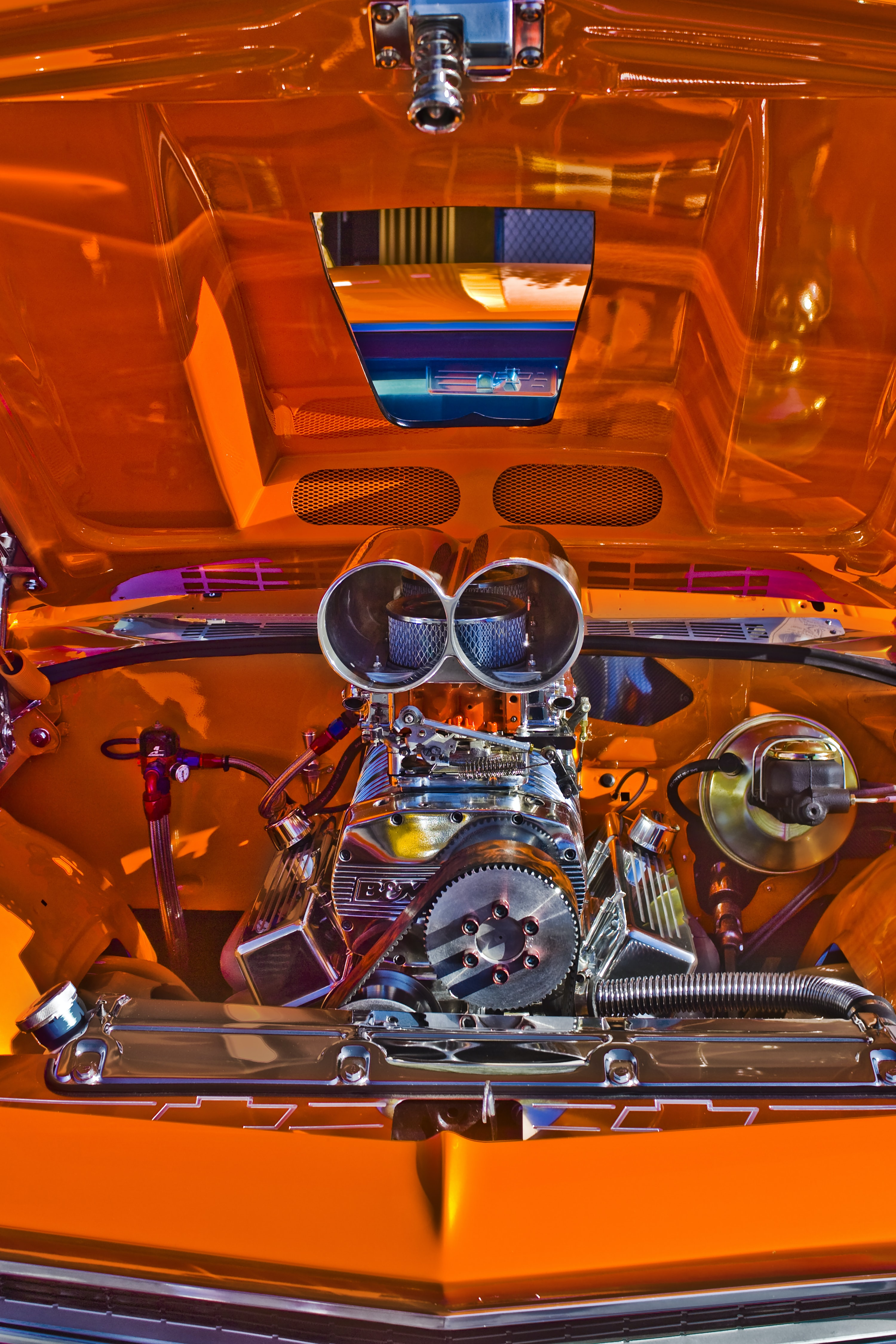Under the hood of an orange car with a shiny metallic engine