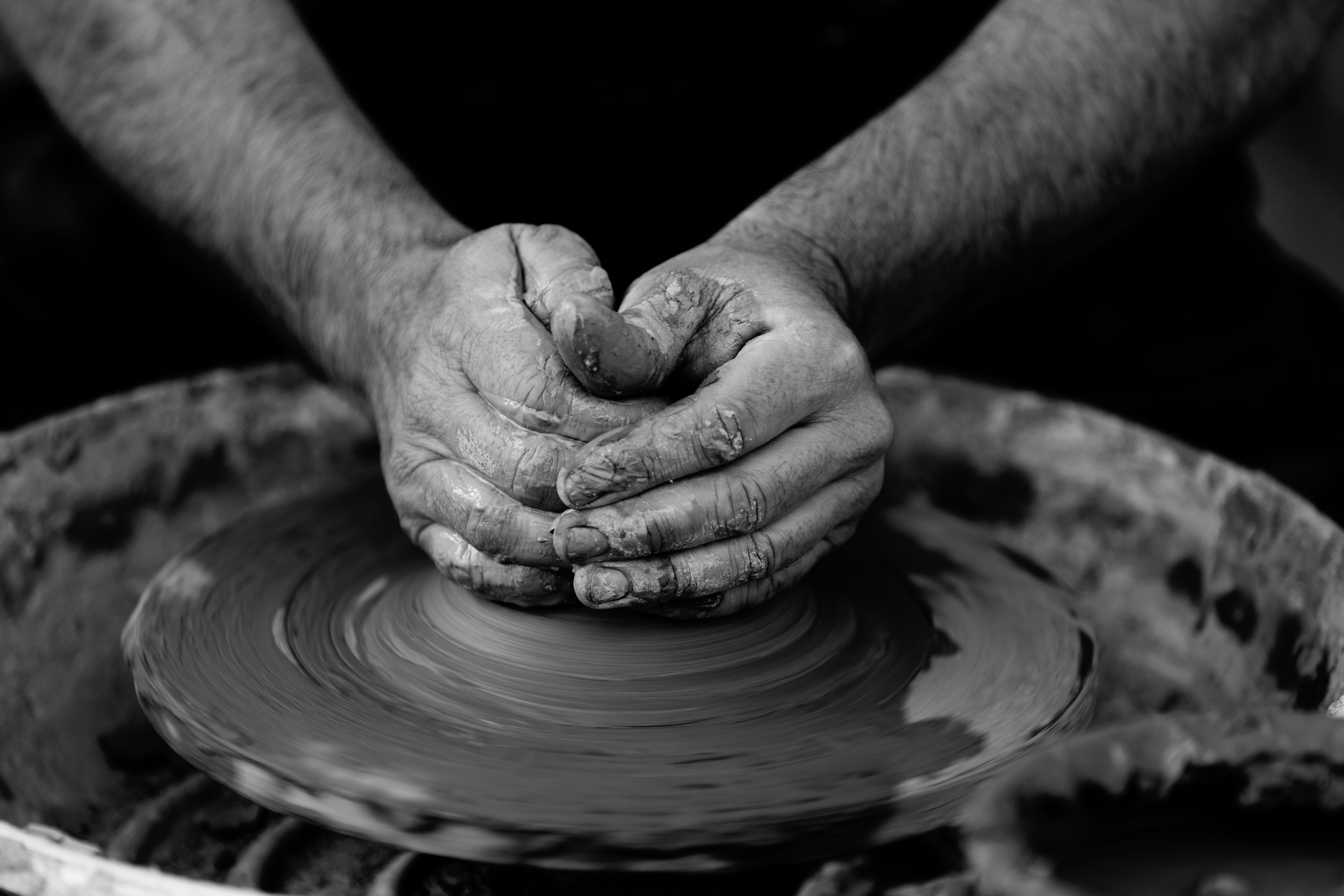 Black and white photo of potter molding clay with his hands on a spinning pottery wheel