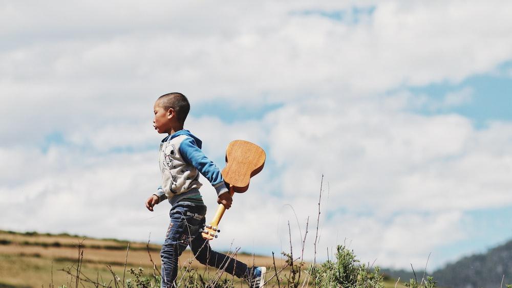 boy running while holding ukelele