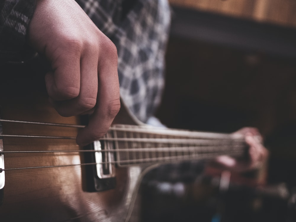 A bleak shot of a person in a checkered shirt strumming a guitar