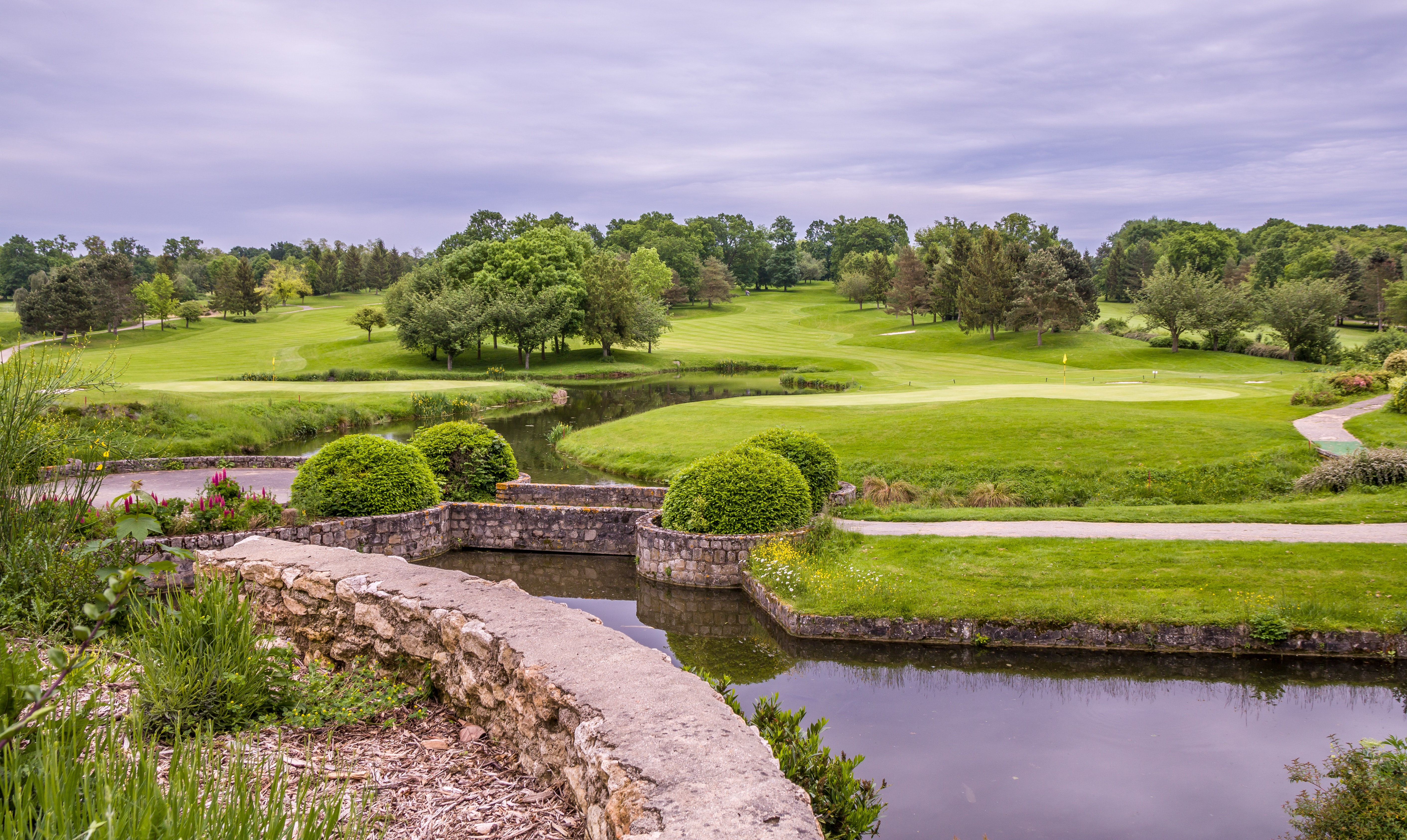 A golf course with holes by the water in Cély