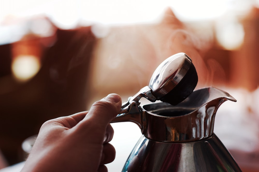 A coffee pot being held and opened to allow steam to escape