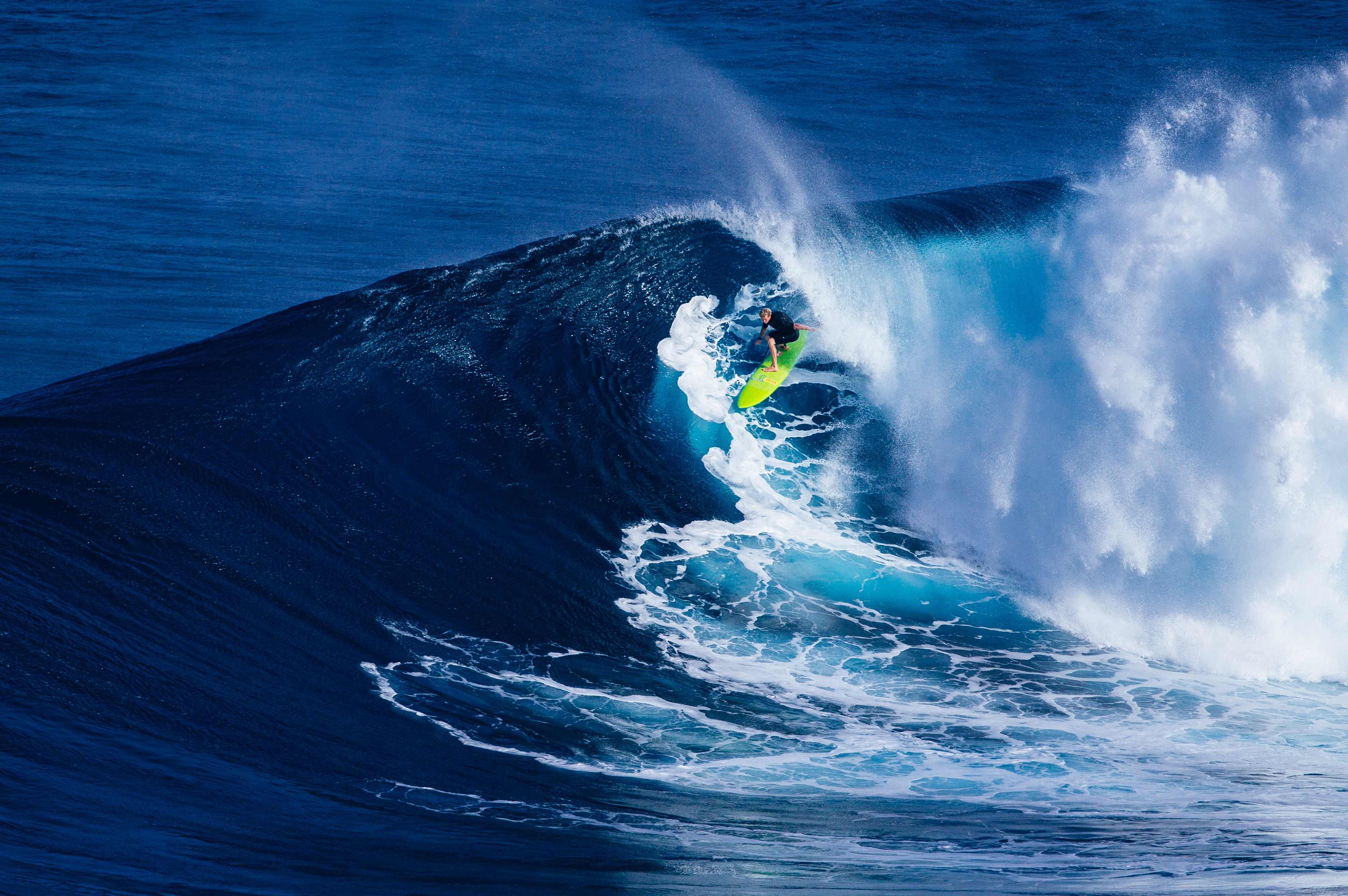 A surfer on a lime green surf board riding a massive blue wave