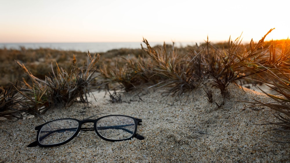 clear eyeglasses with black frames on sand