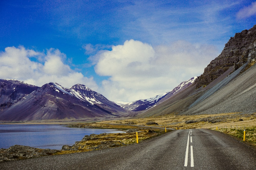 road going to mountain near body of water