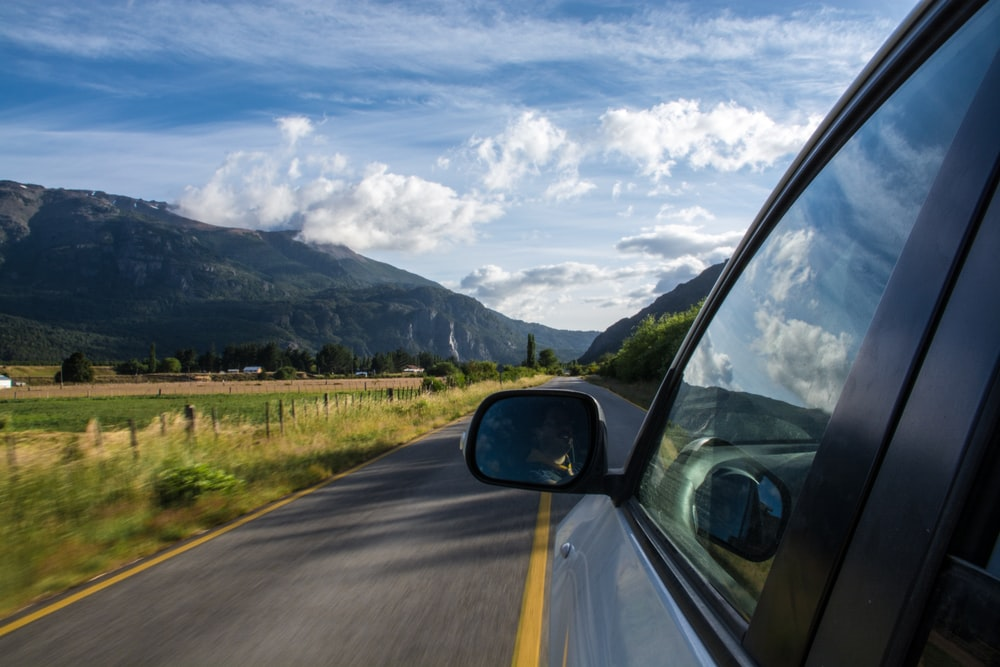 A view from the side of a car driving on a rural road in the mountains