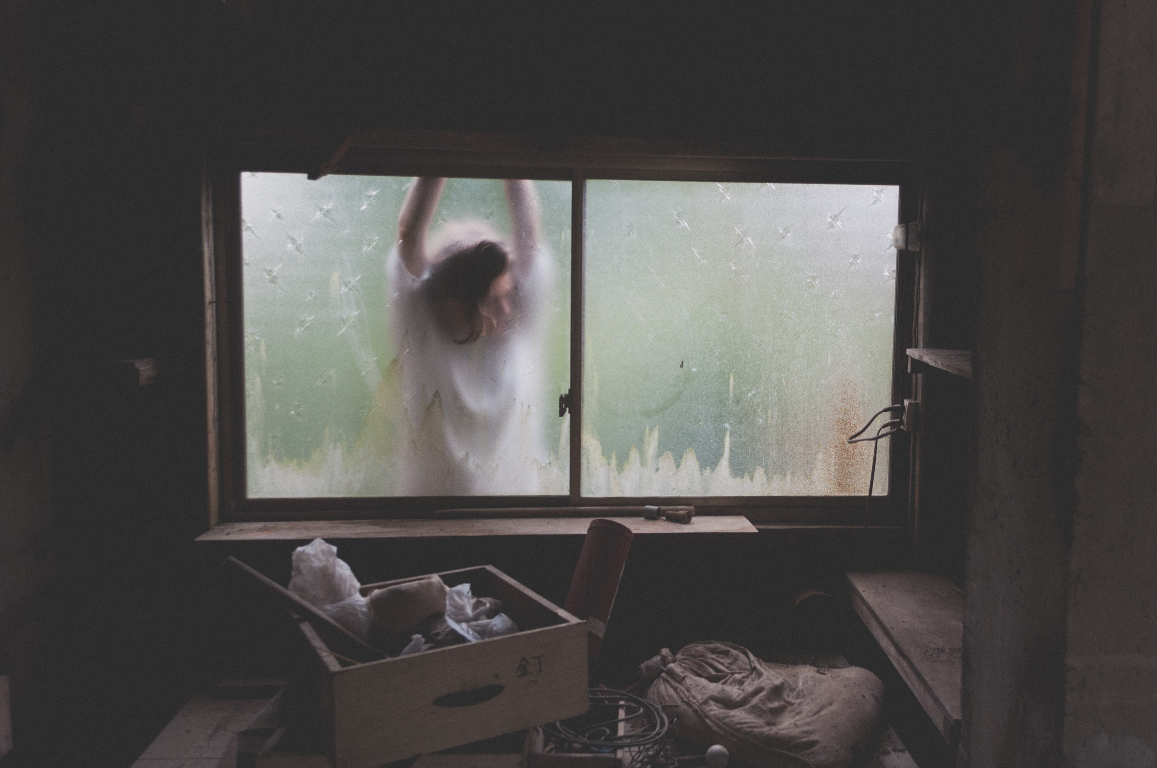 A spooky shot of a helpless looking woman clawing at a window from the outside, with the interior of the room covered in boxes