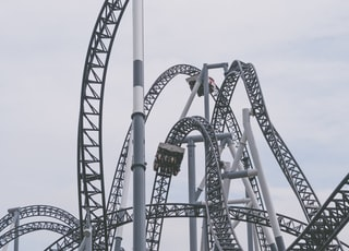 roller coaster under white clouds and blue sky