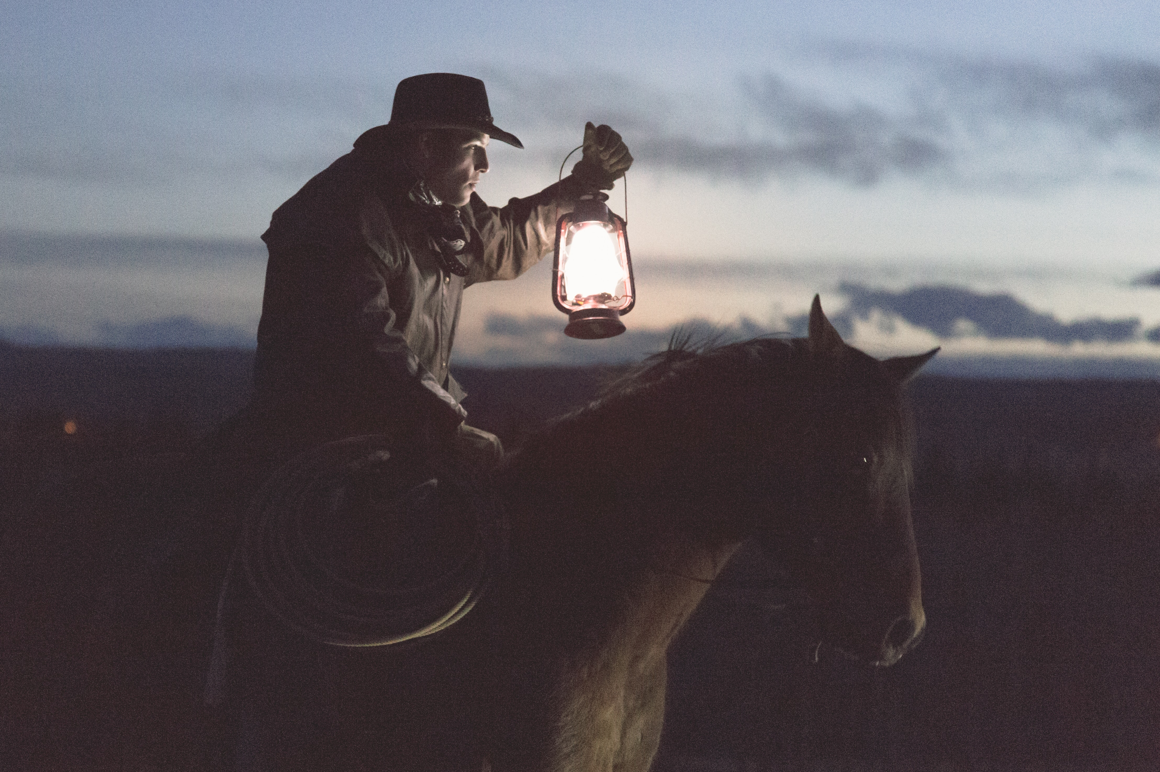 A man in a cowboy hat holds a lasso in one hand and a lamp in another while riding a horse