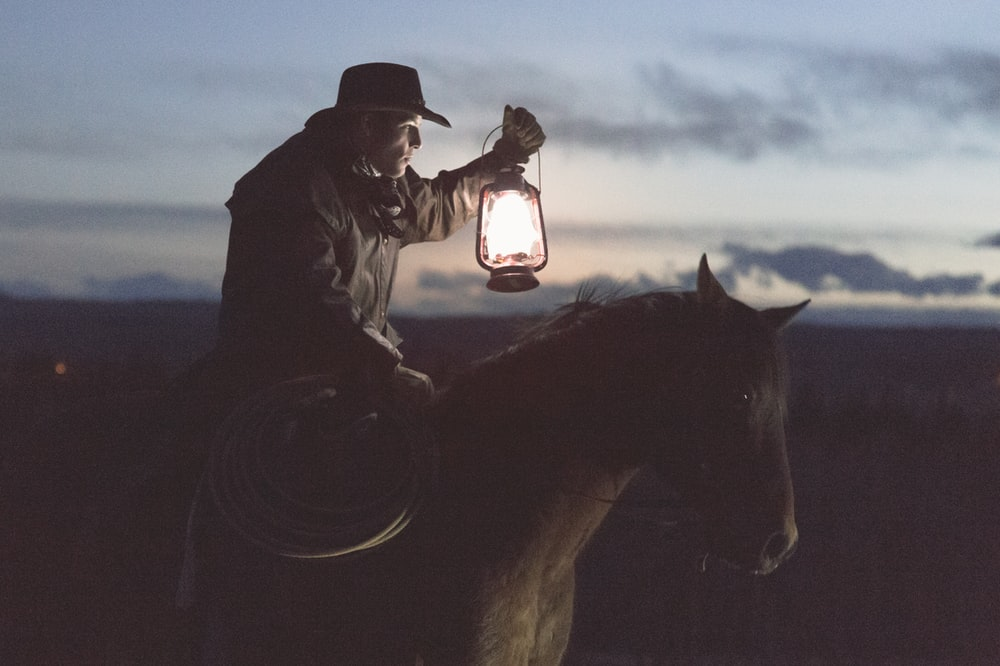 man riding horse holding lantern