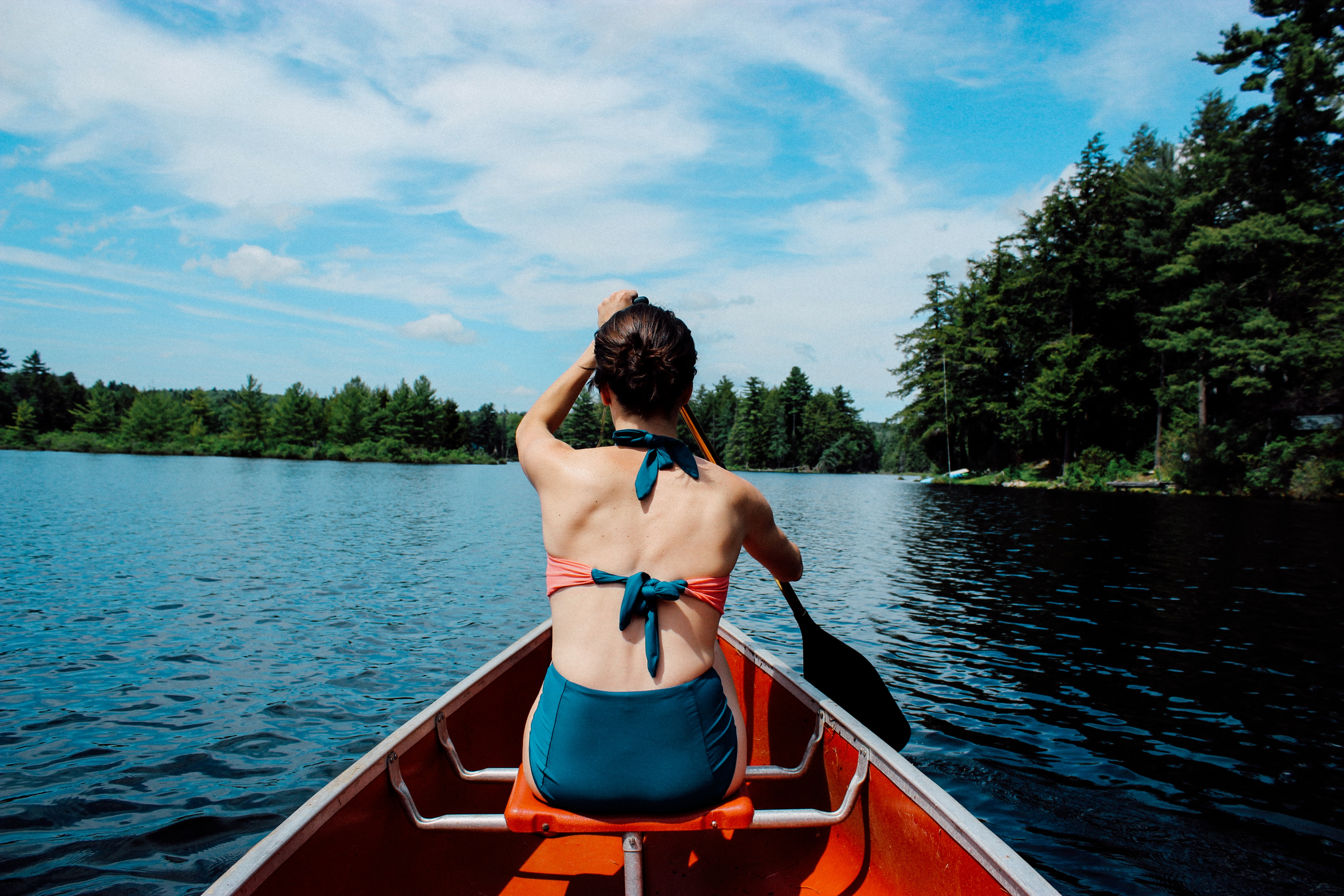 woman riding on boat while paddling under blue sky during daytime