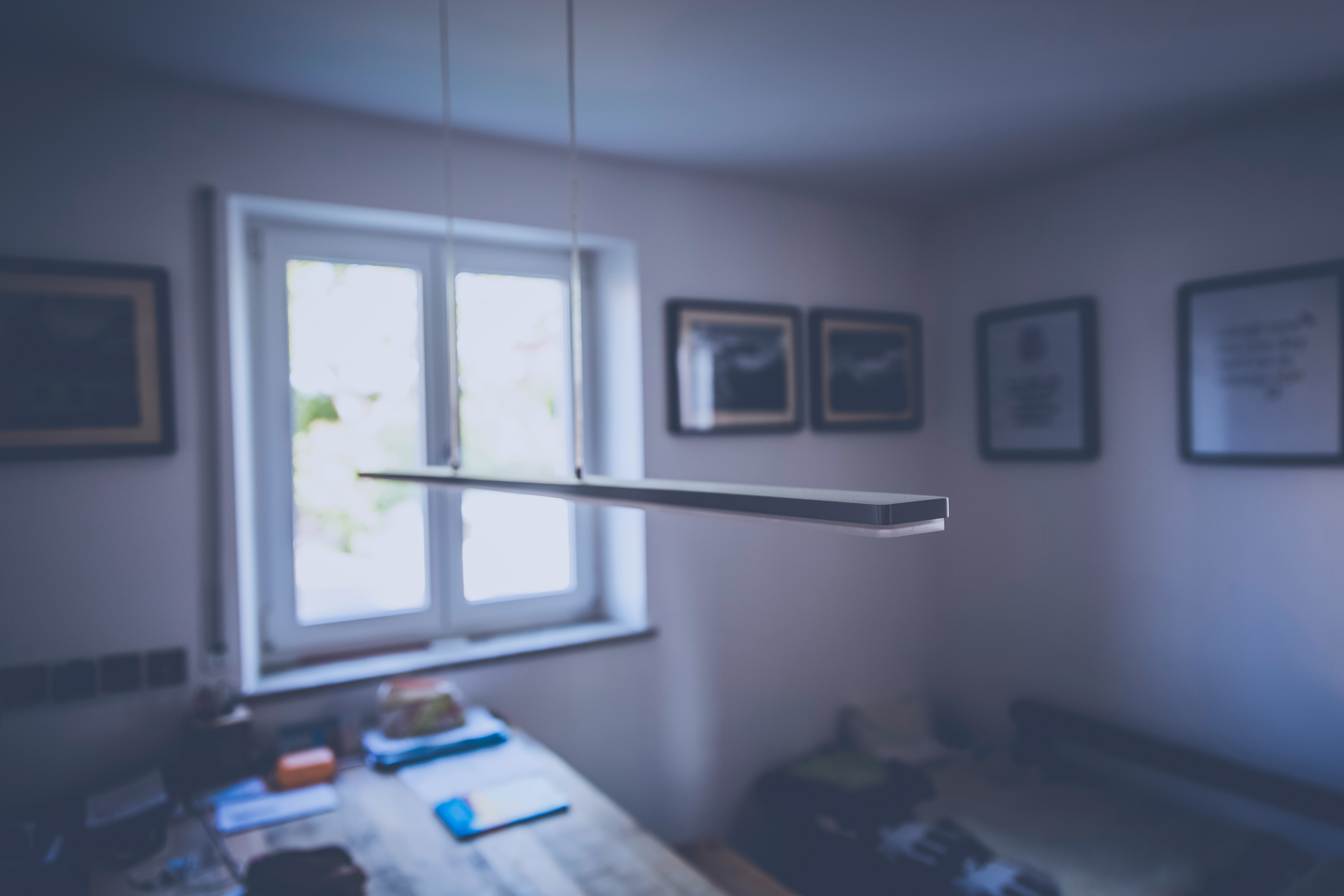 Ceiling lamp hangs down in an empty room with a table