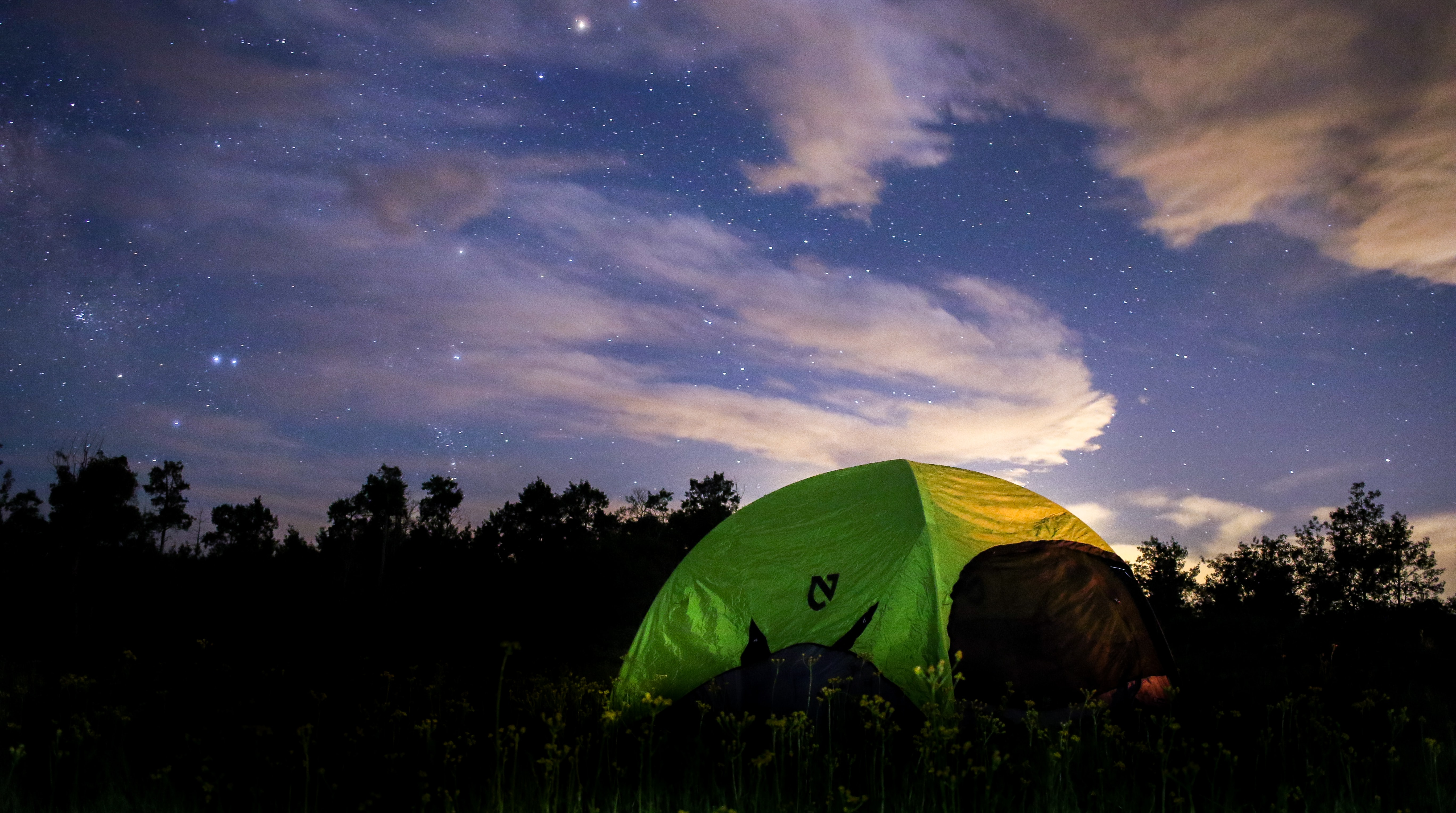 A green tent in a field under a starry sky with fluffy clouds