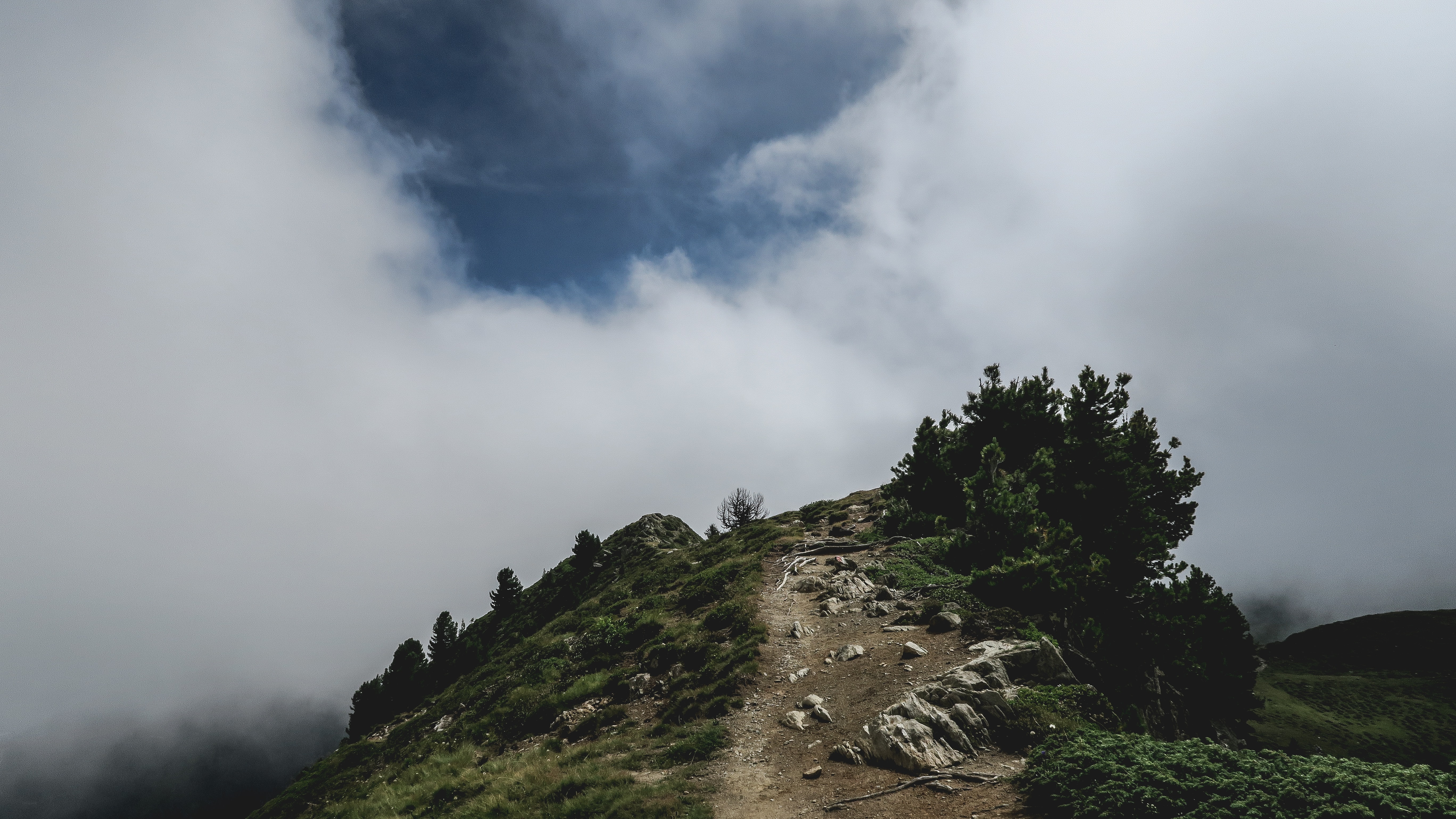 Rocky hiking path on a grassy hillside leads to clouds