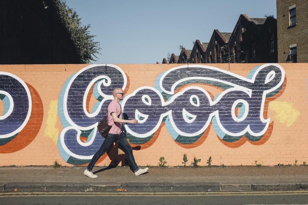 man walking beside graffiti wall