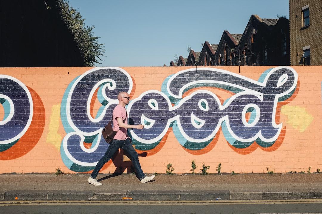 Bald man walks in front of graffiti