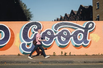 man walking beside graffiti wall good teams background