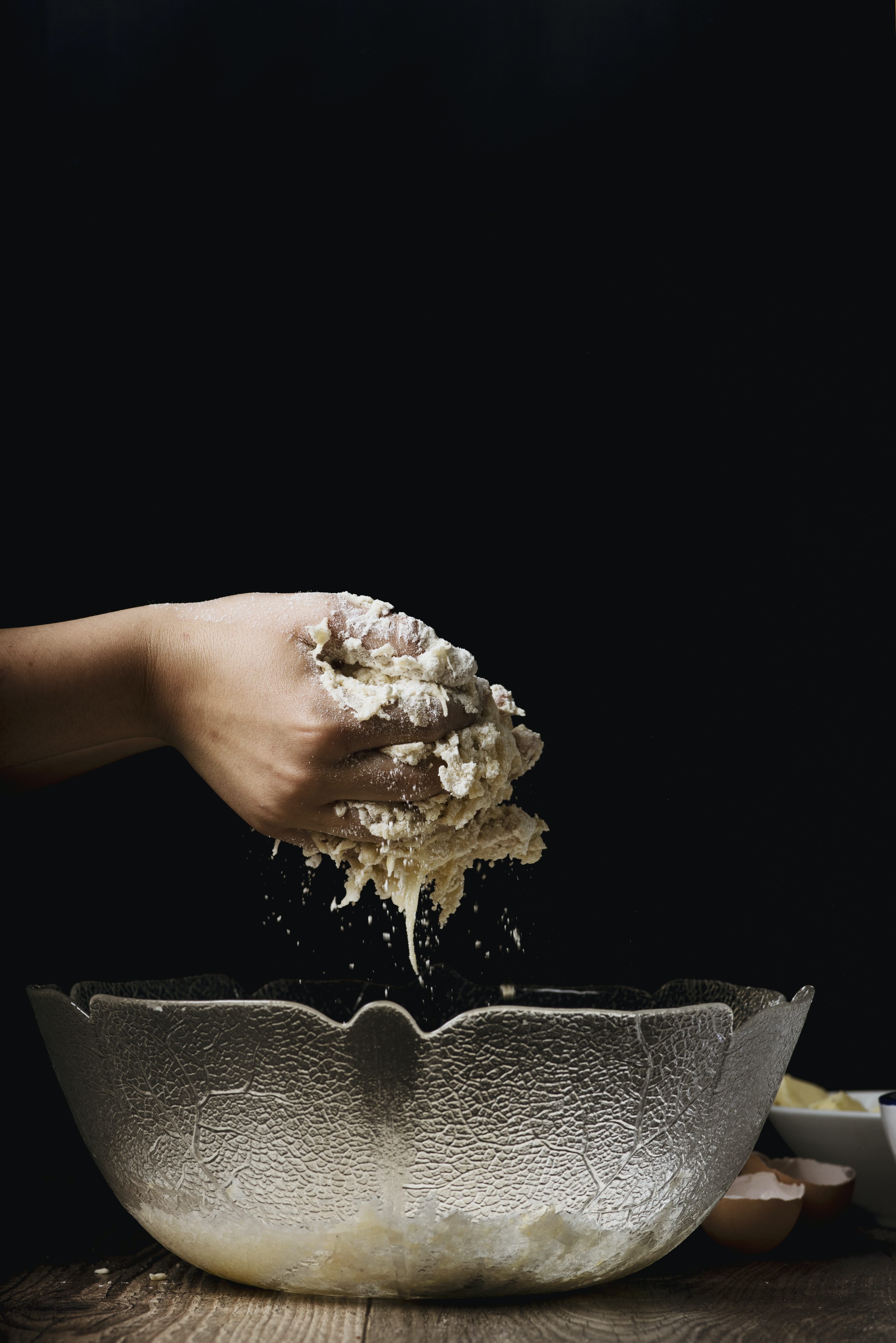 A person's hand kneading dough over a glass bowl
