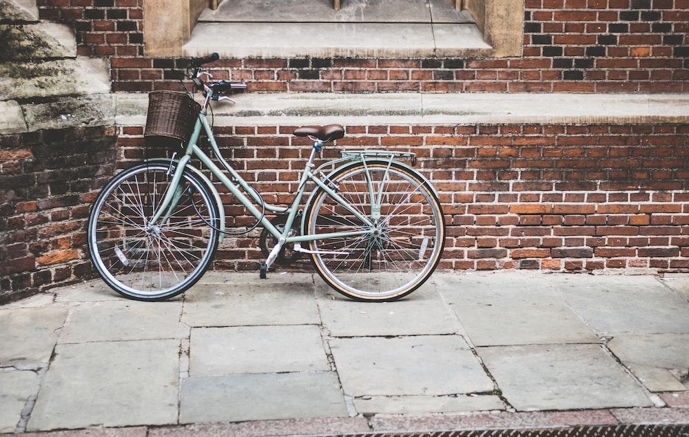 photo of parked blue commuter bike on gray brick wall