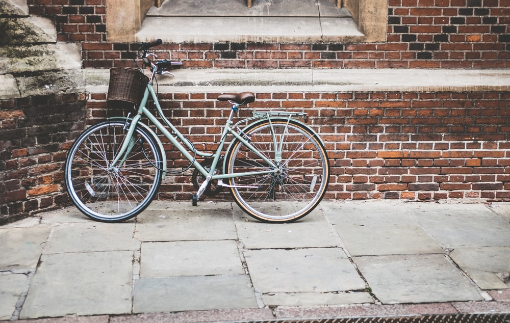photo of parked blue commuter bike on gray brick wall