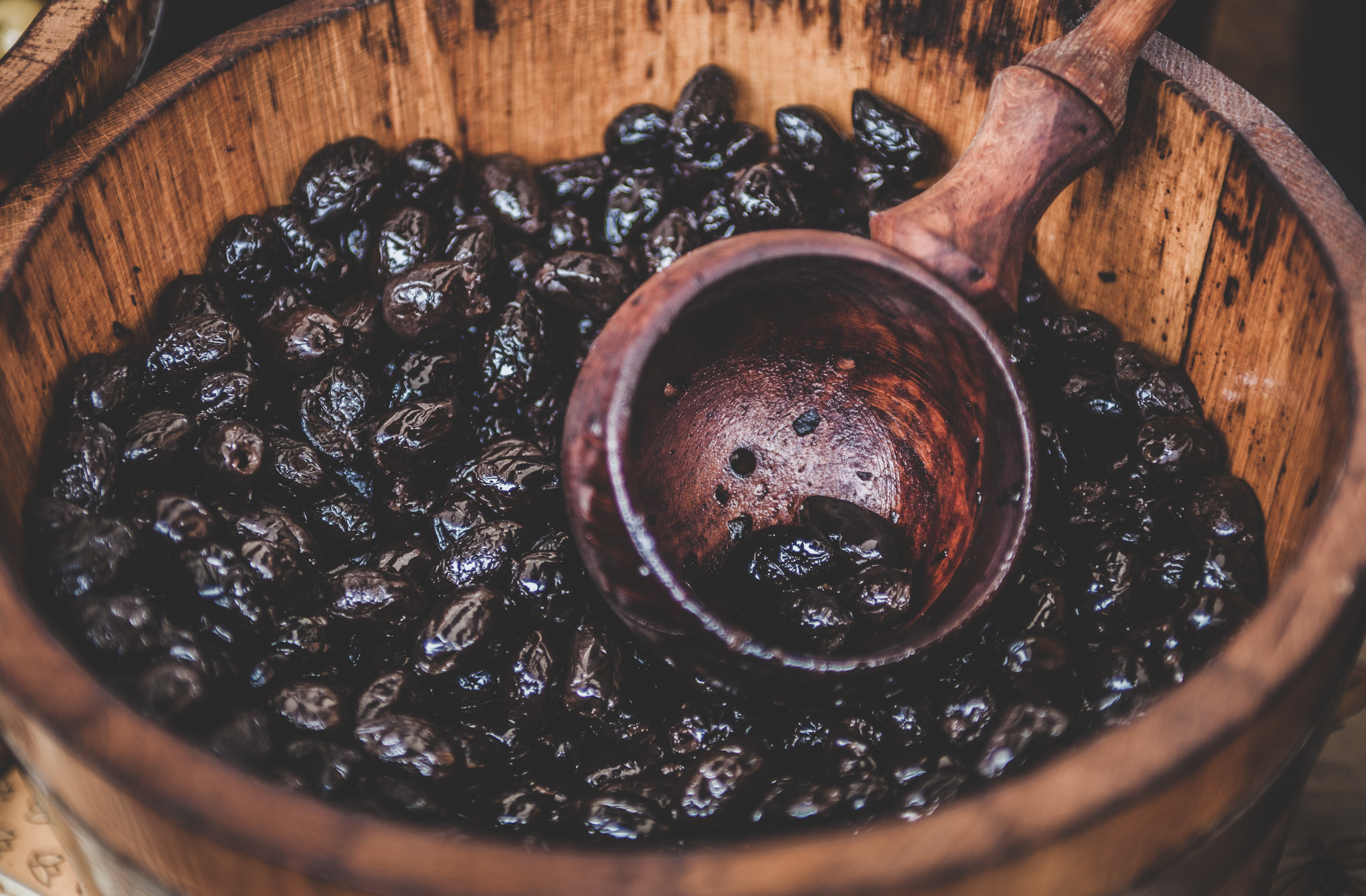 A close-up of a bucket full of cocoa beans and a wooden ladle in Cambridge.