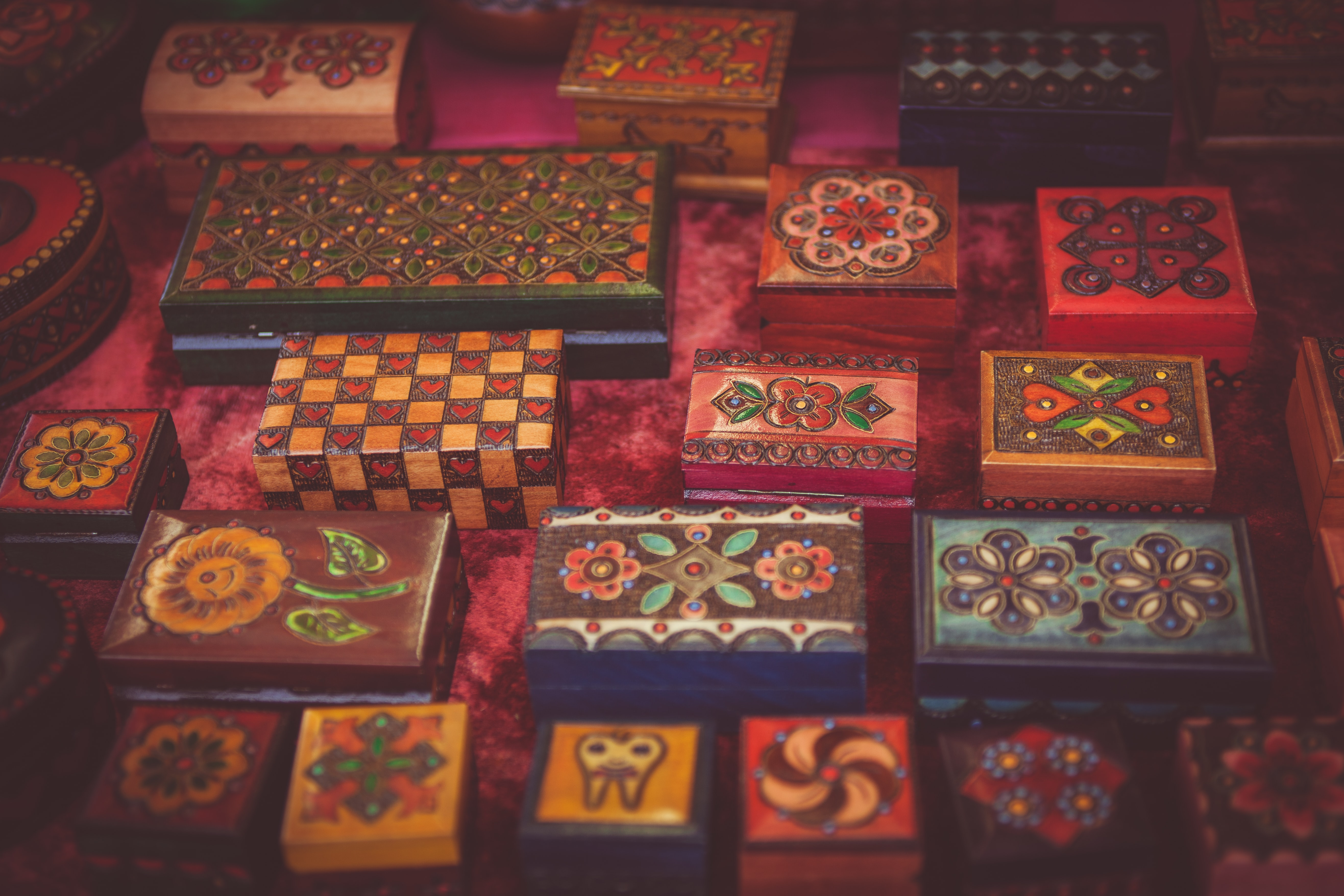 Assorted woodwork boxes collection with varied floral art designs on red fabric surface in Cambridge
