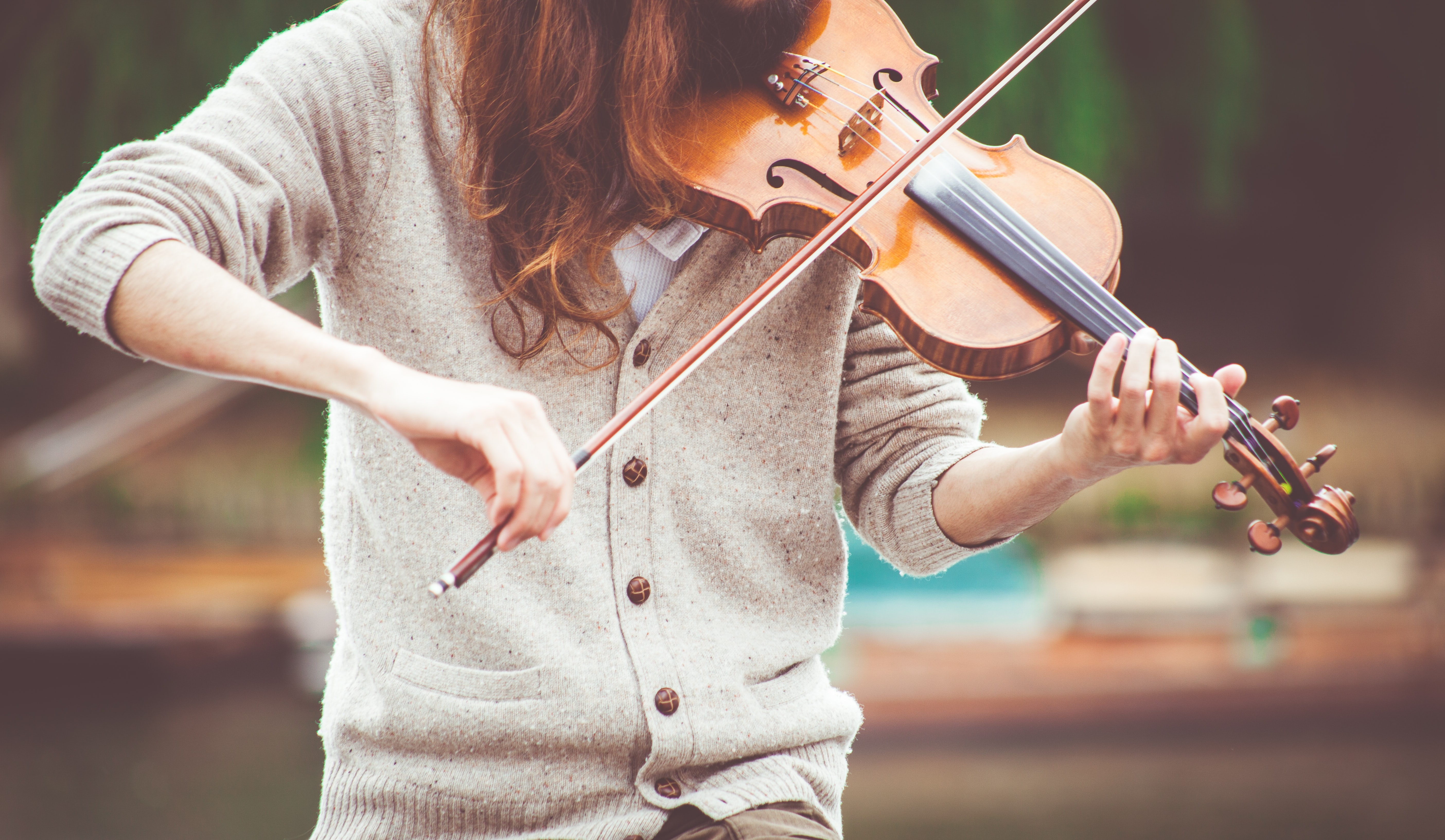A person in a grey sweater playing the violin outdoors