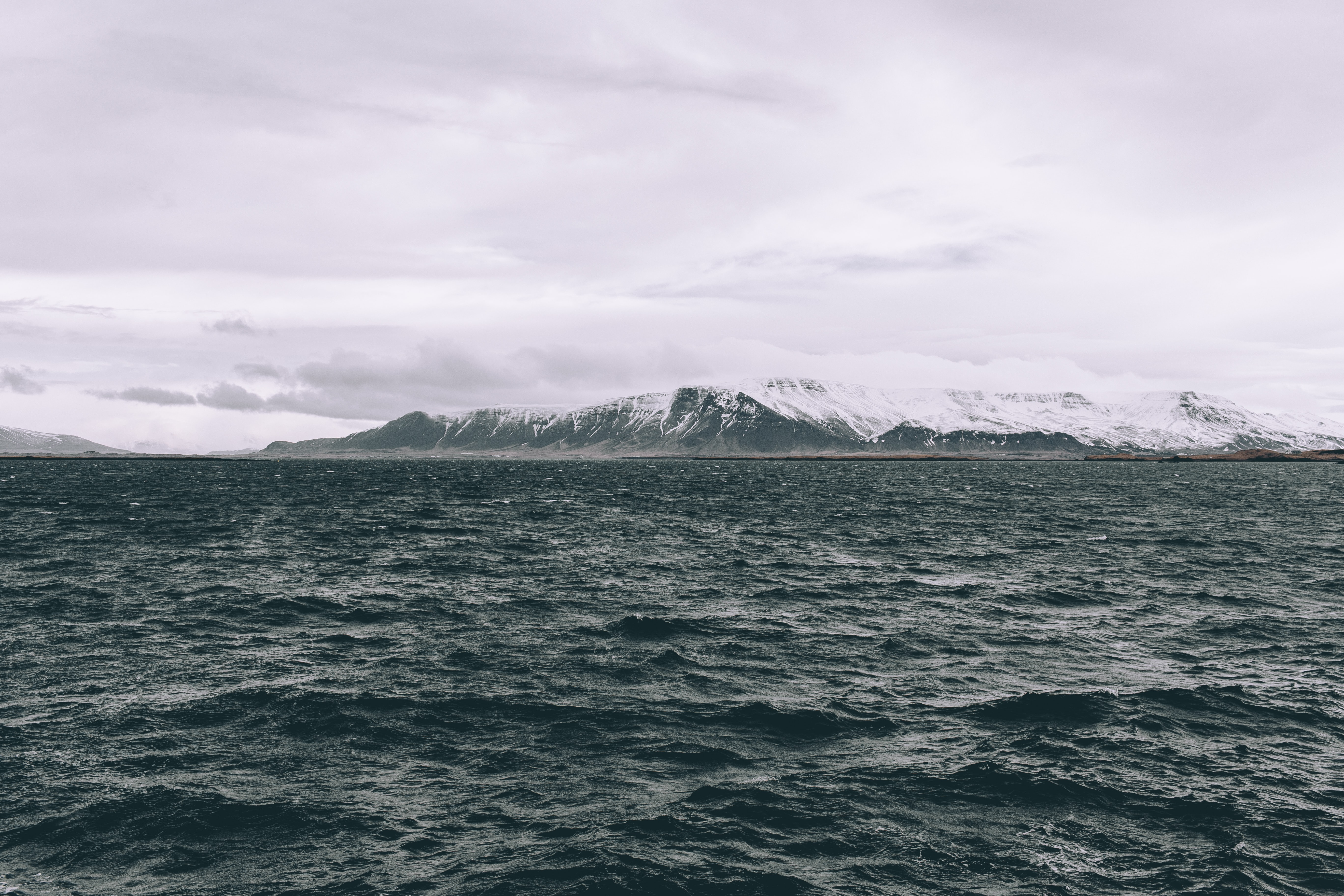 Ocean around cloudy Iceland with snow capped rocks and mountains at the horizon