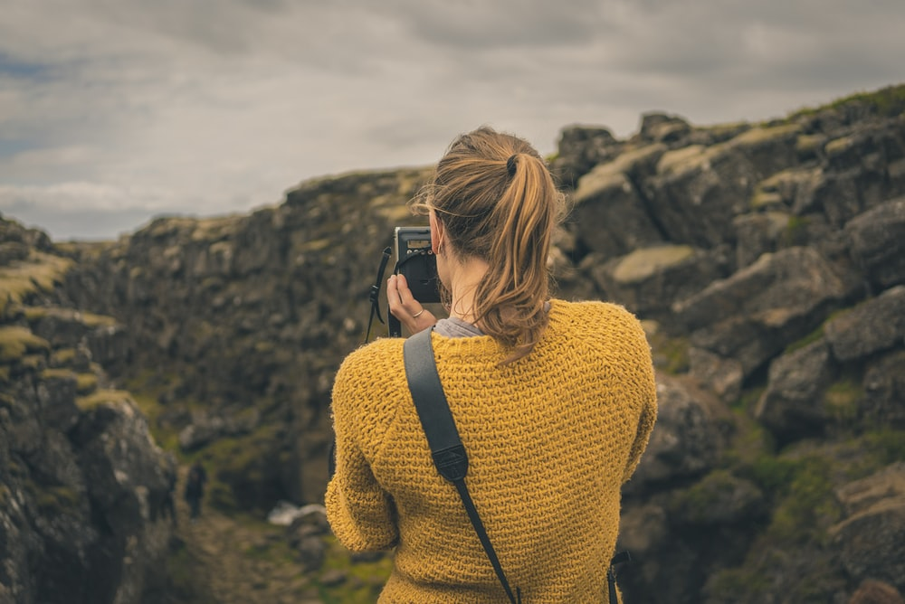 woman taking picture of mountain